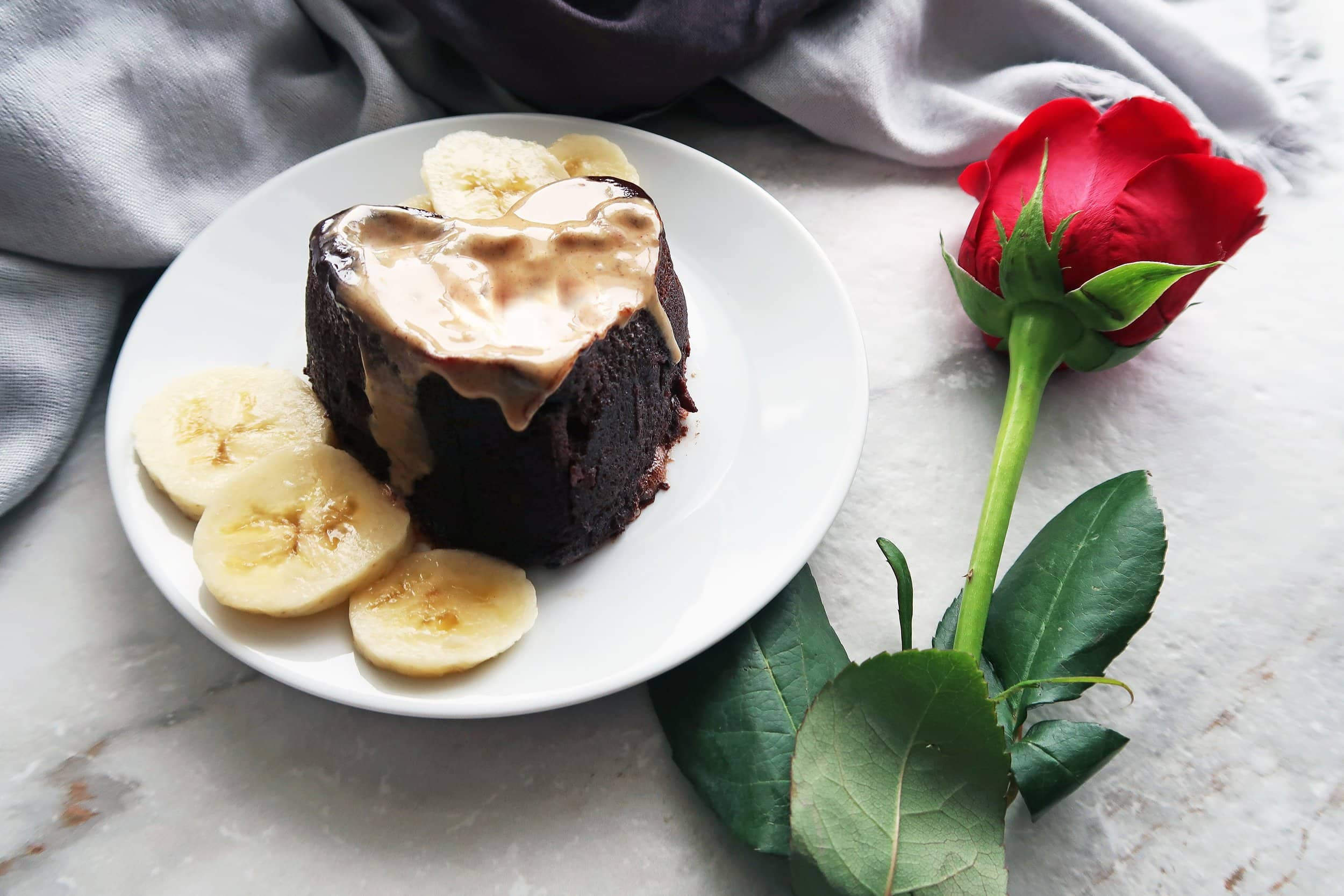 A peanut butter banana chocolate mini cake on a plate next to a rose.