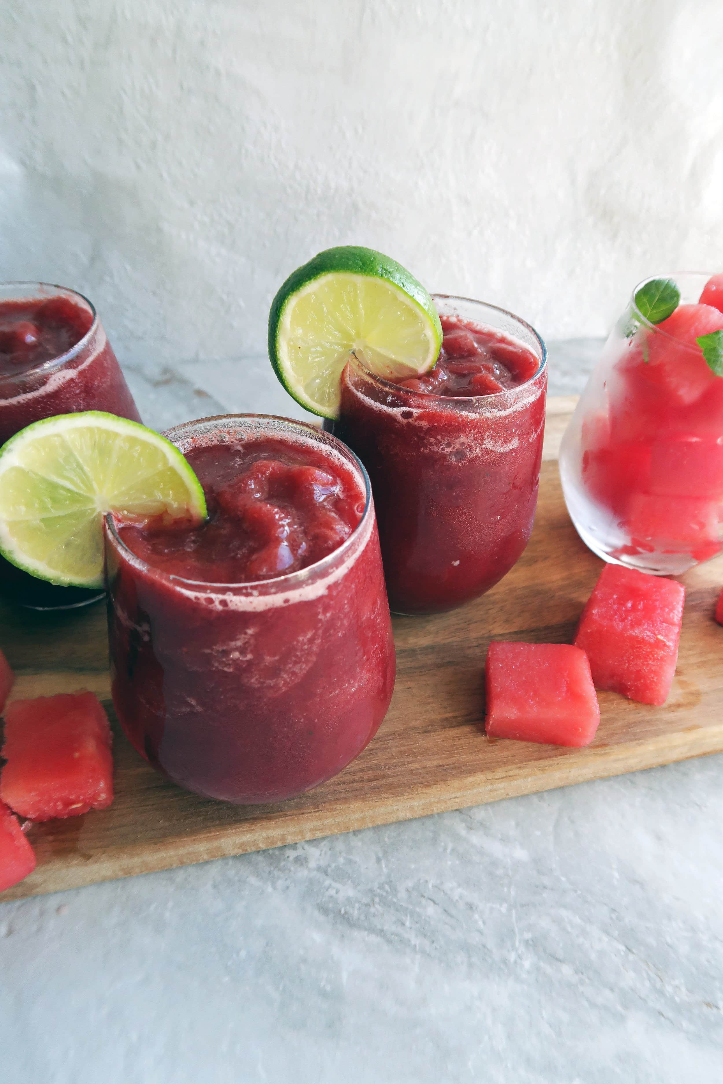 Three Watermelon Cherry Slushies in round glass cups on a wooden board with watermelon cubes around it.