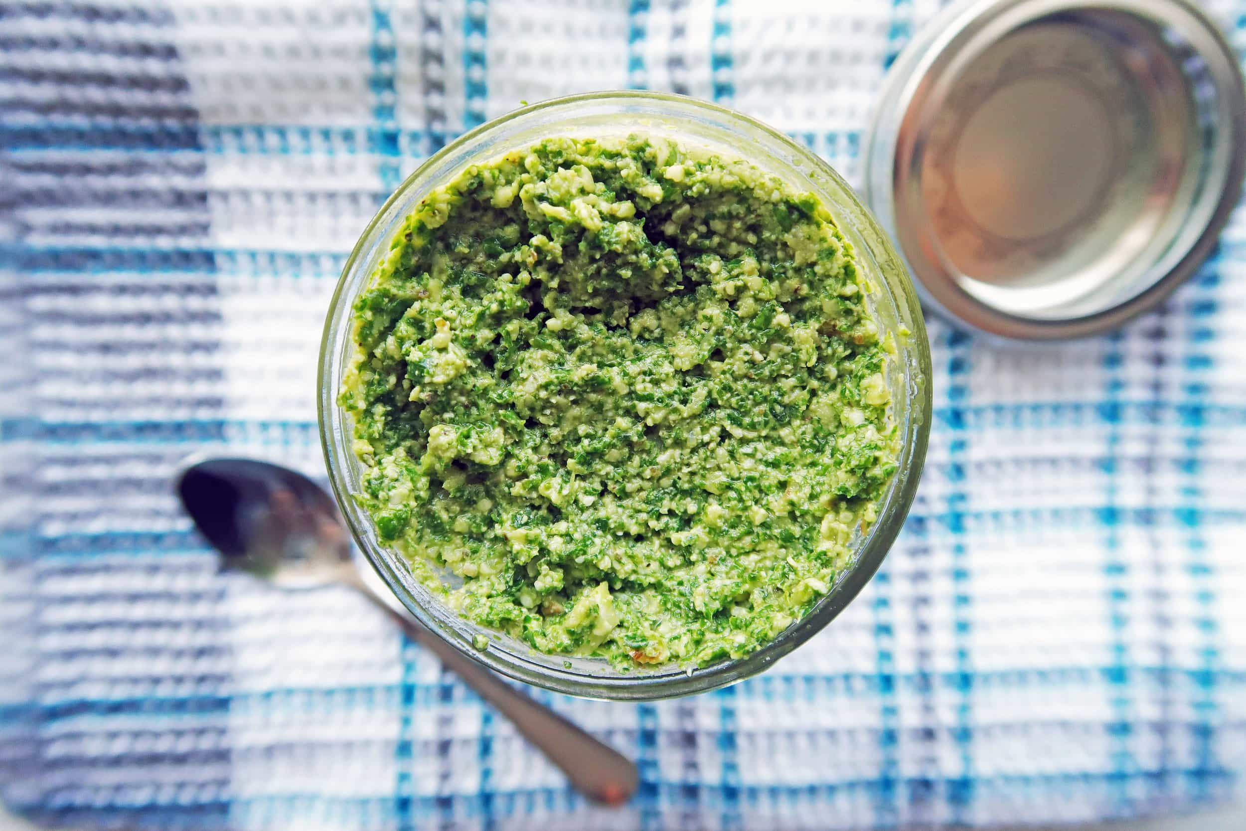 Overhead view of 5 Minute Kale Walnut Pesto in a mason jar; a small spoon to its side.