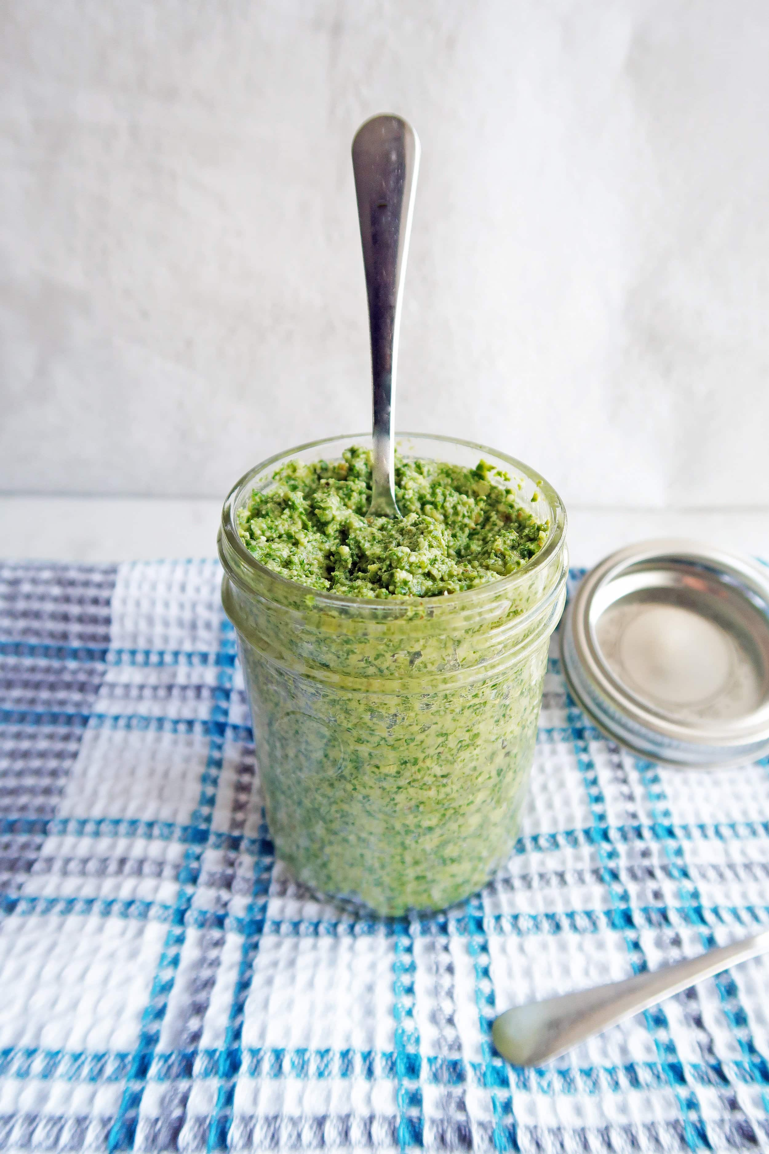 5 Minute Kale Walnut Pesto in a tall mason jar with a spoon sticking upright in the pesto.