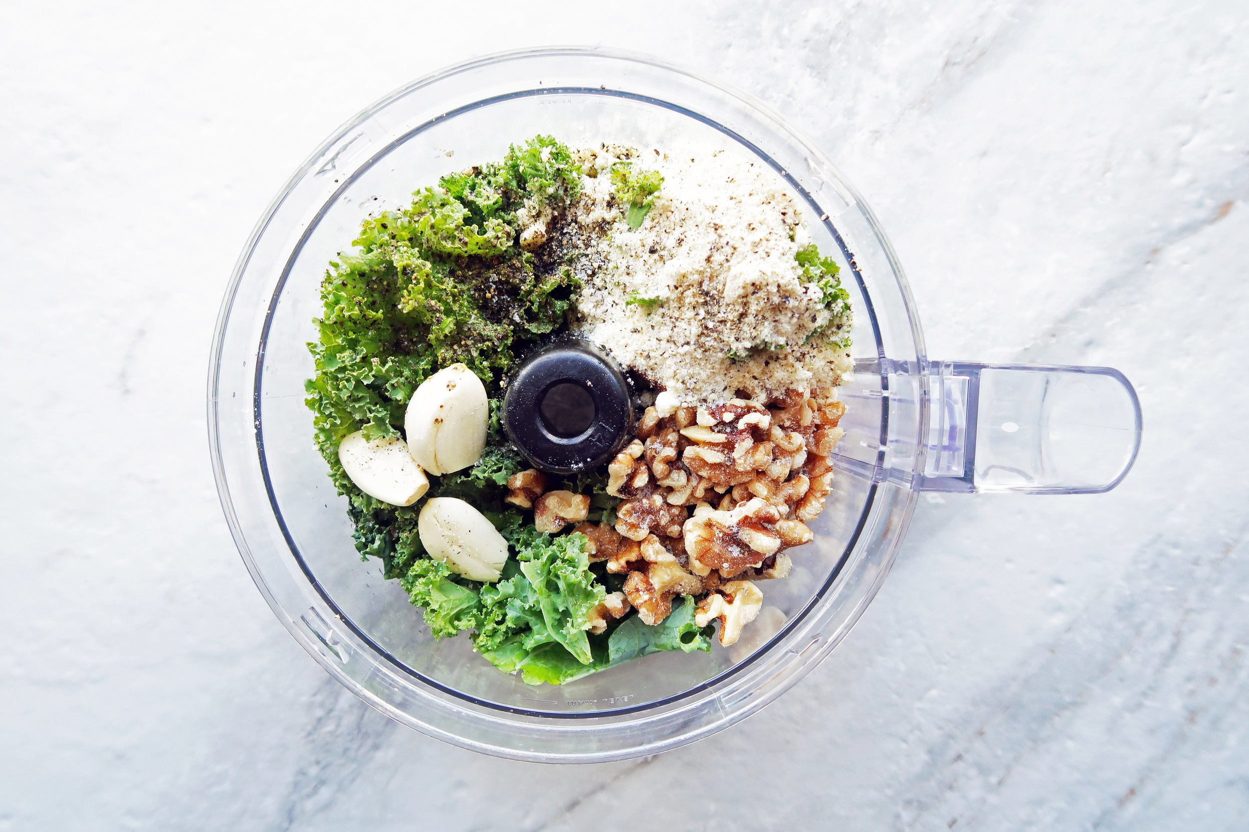 Kale walnut pesto ingredients in a food processor.