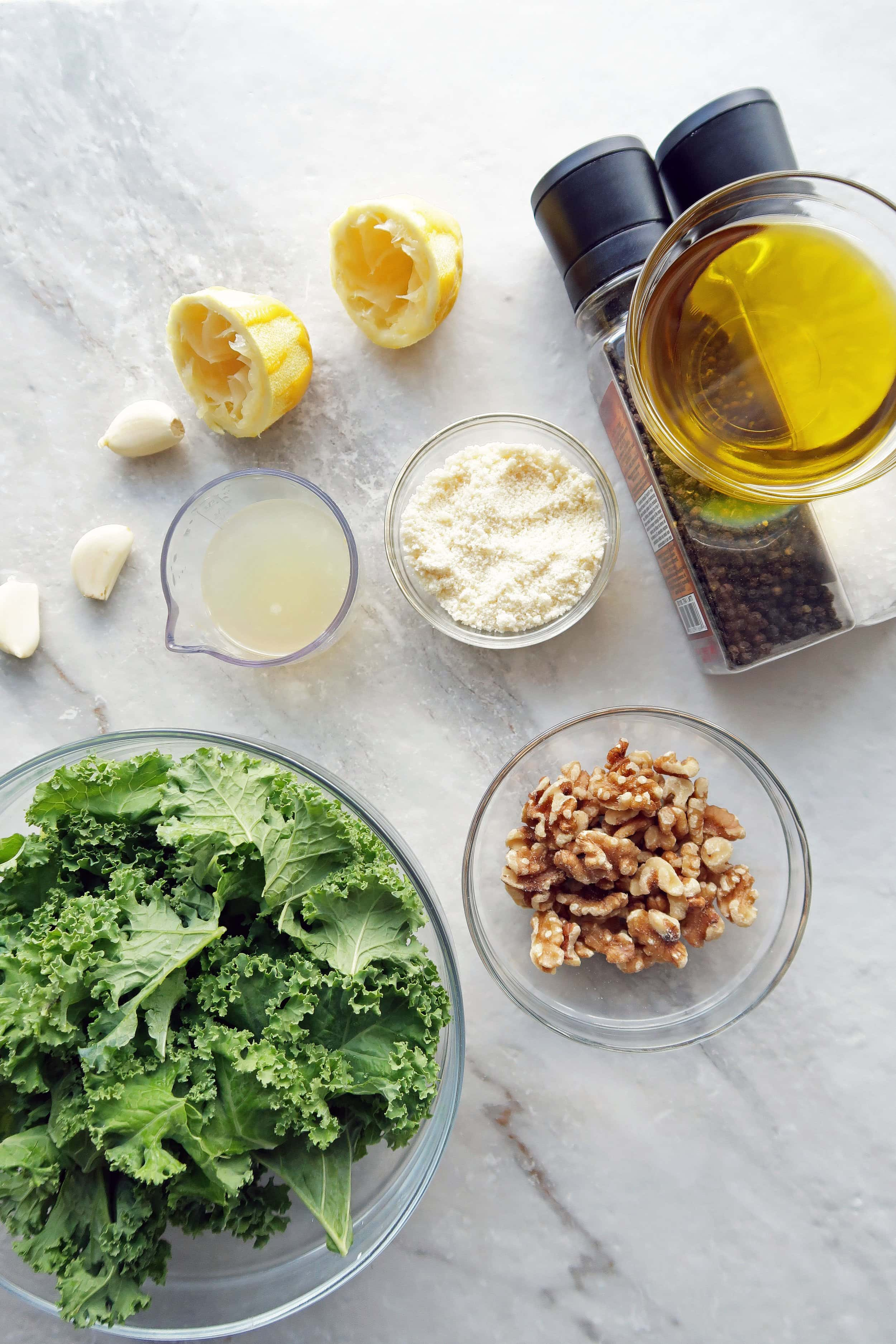 Bowls of kale, walnuts, olive oil, lemon juice, and parmesan cheese along with loose garlic and salt and pepper shakers.