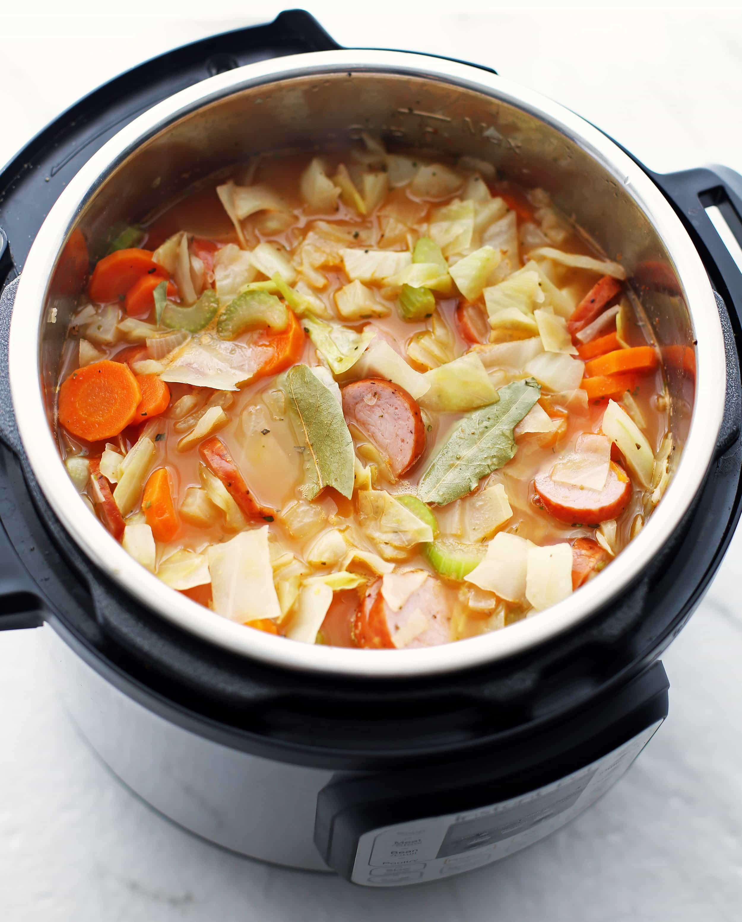 Prepared ingredients for fennel, cabbage, and sausage soup placed in the Instant Pot, which includes carrots, celery, onions.
