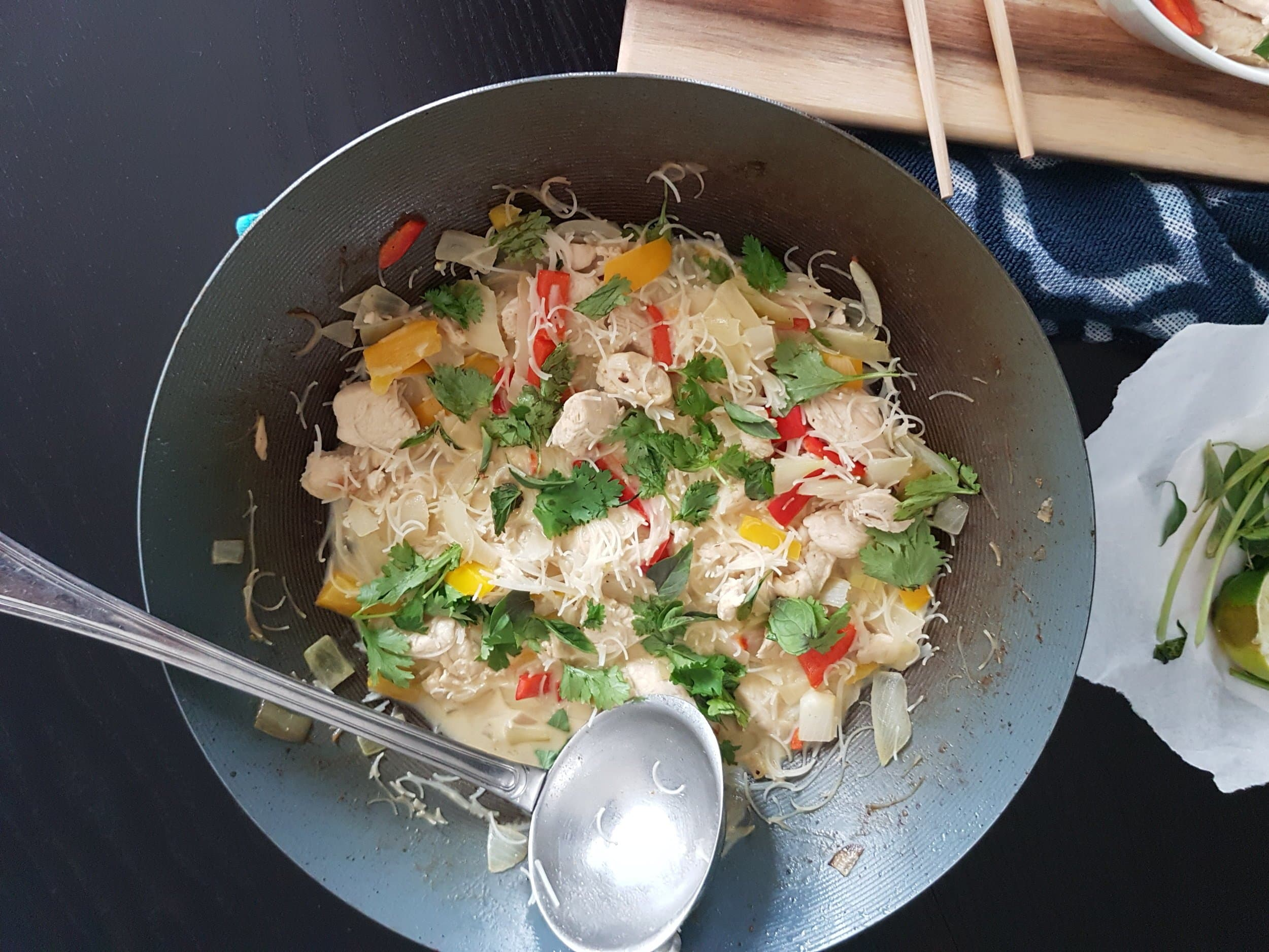A wok full of Thai Green Coconut Curry Chicken with Rice Noodles.
