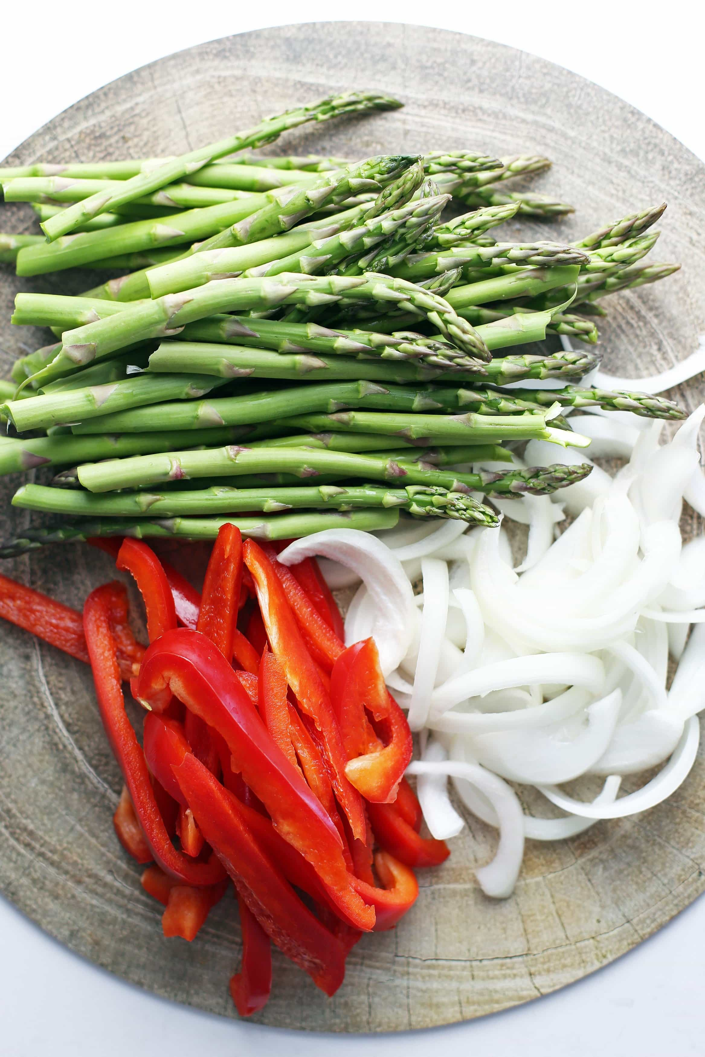 Sliced red bell pepper, sliced white onion, and trimmed asparagus on a round wooden platter.