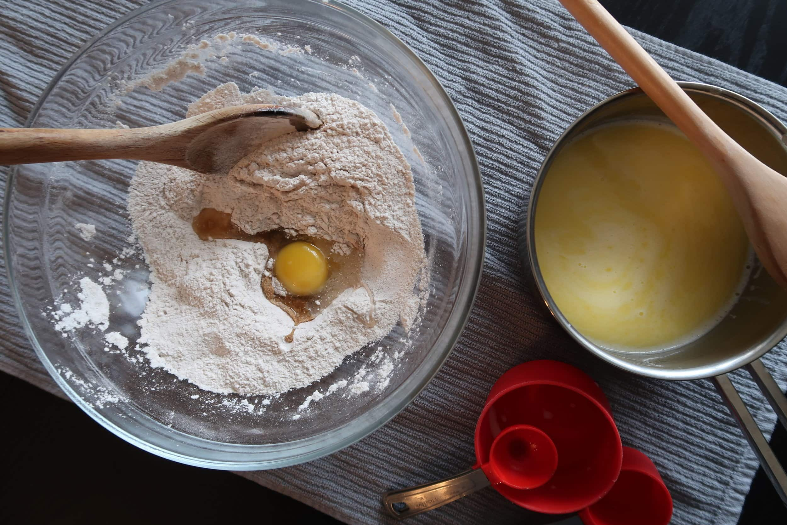 Eggs being added to the dry ingredients for cinnamon roll dough.