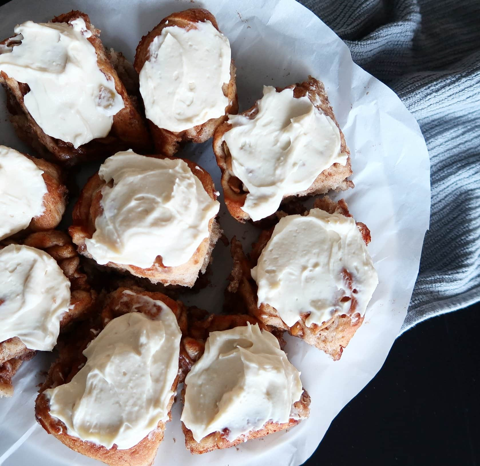 A plate of Apple Cinnamon Rolls with Maple Cream Cheese Frosting.