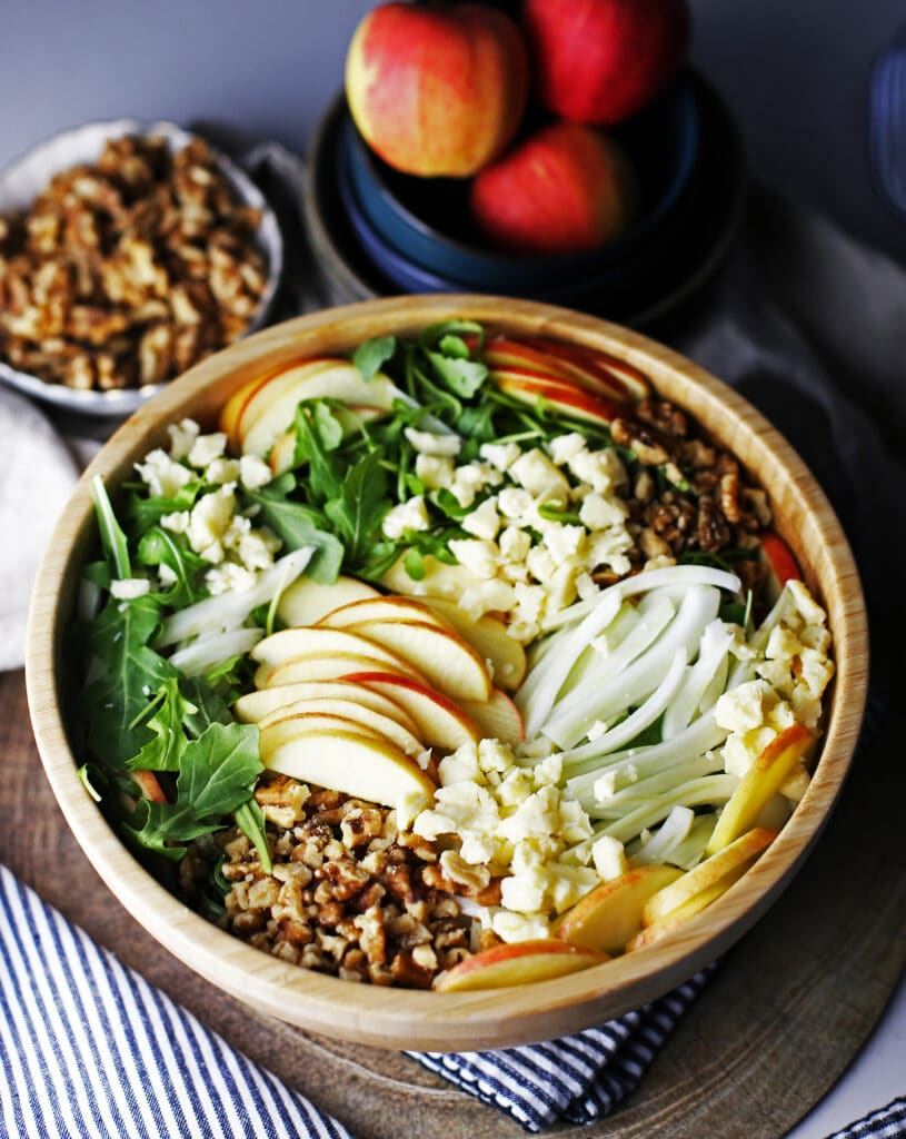 A large bowl of apple fennel arugula salad, a small bowl of walnuts, and three gala apples in a blue bowl.