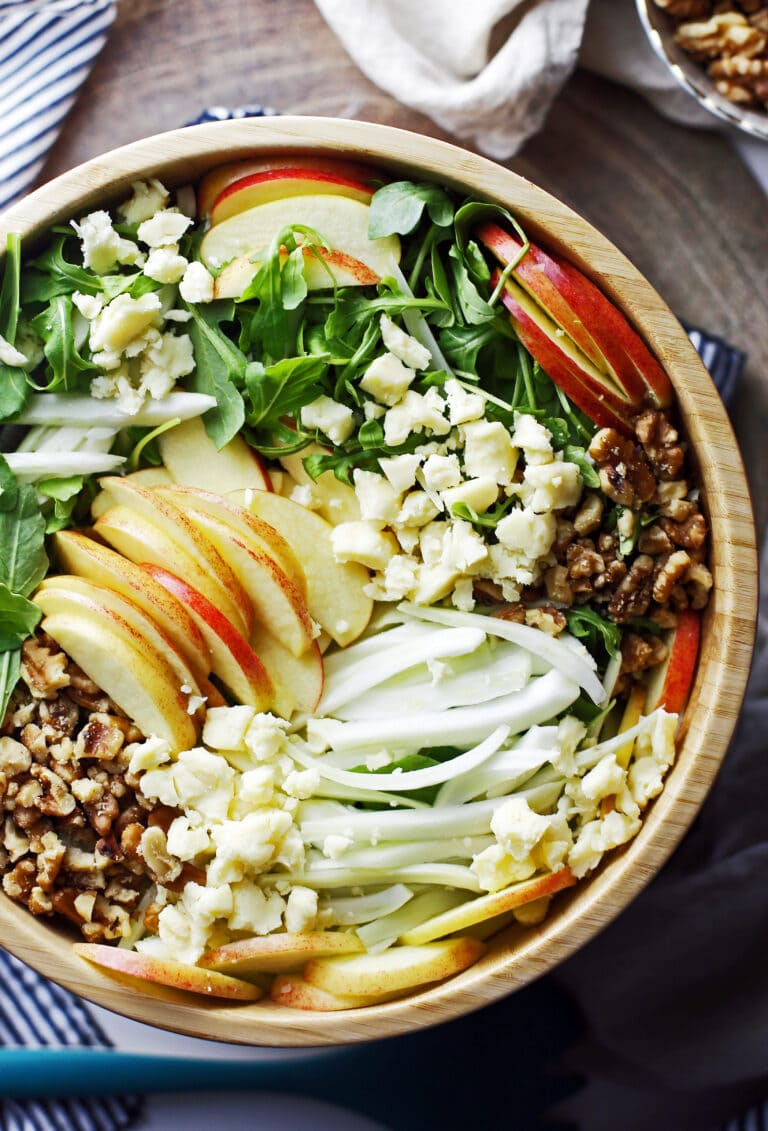 Apple fennel arugula salad with honey lemon vinaigrette in a large wooden bowl.