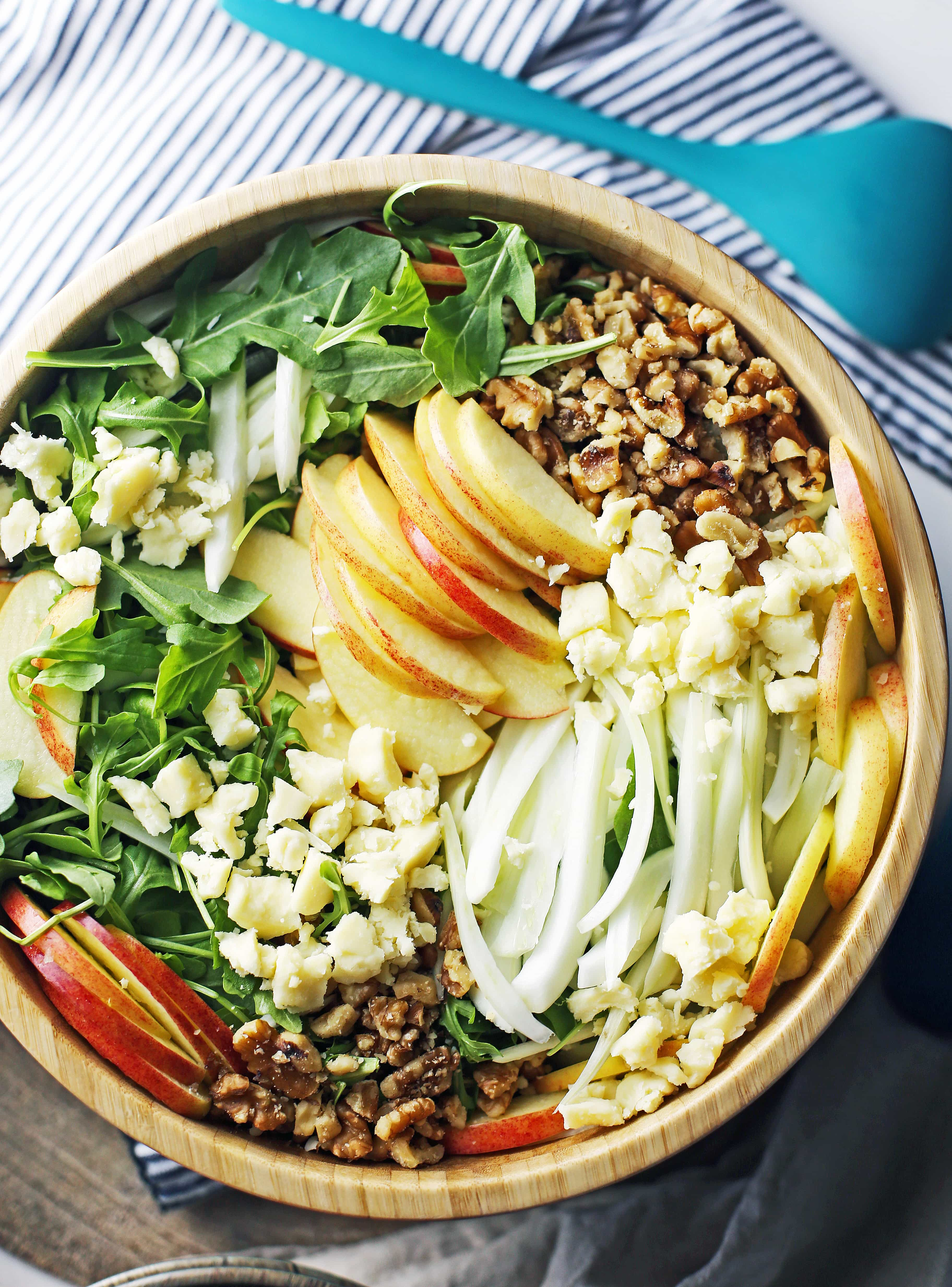 A big wooden bowl containing fennel arugula salad with apples and walnuts.