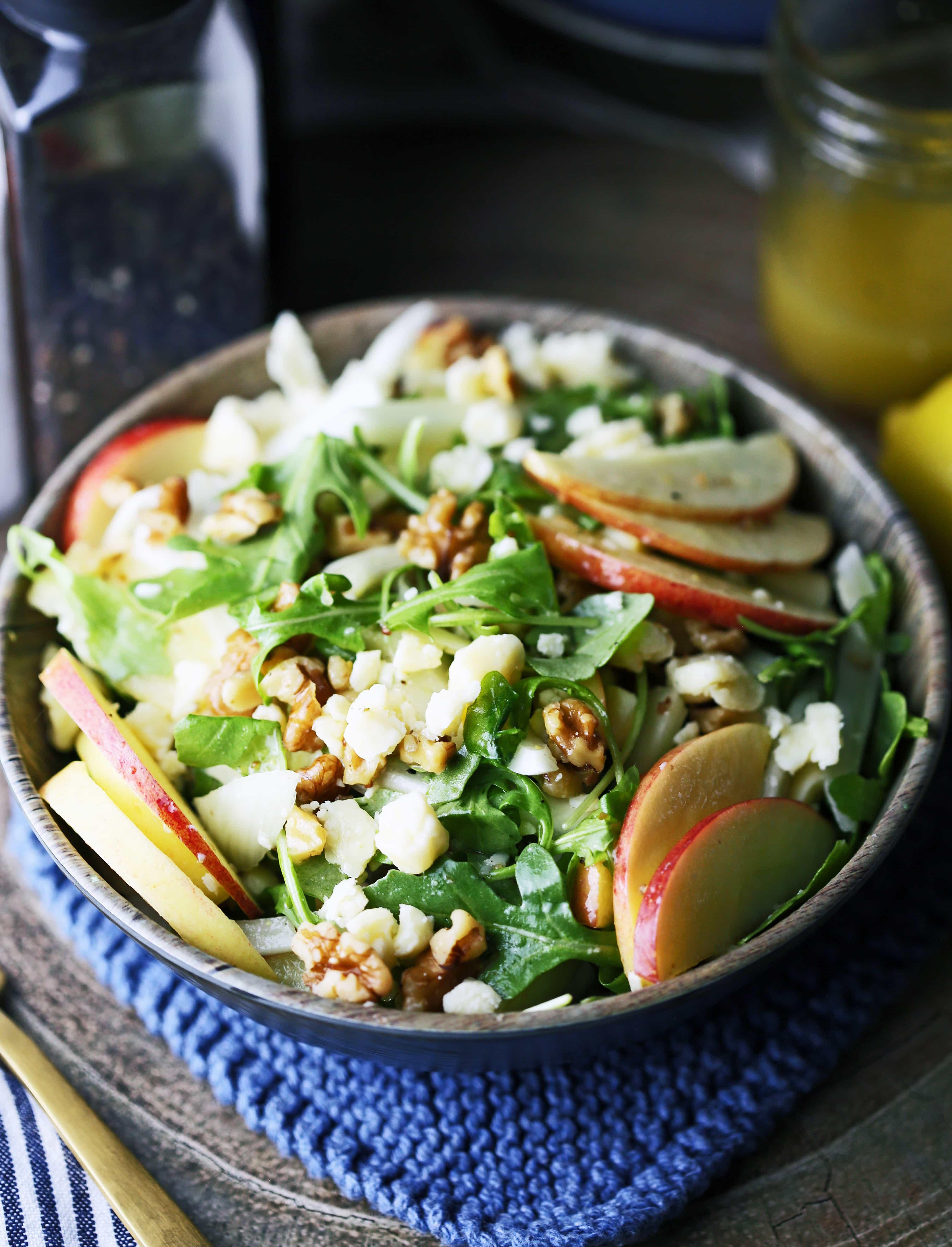 Apple fennel arugula salad with honey lemon dressing in a brown bowl.