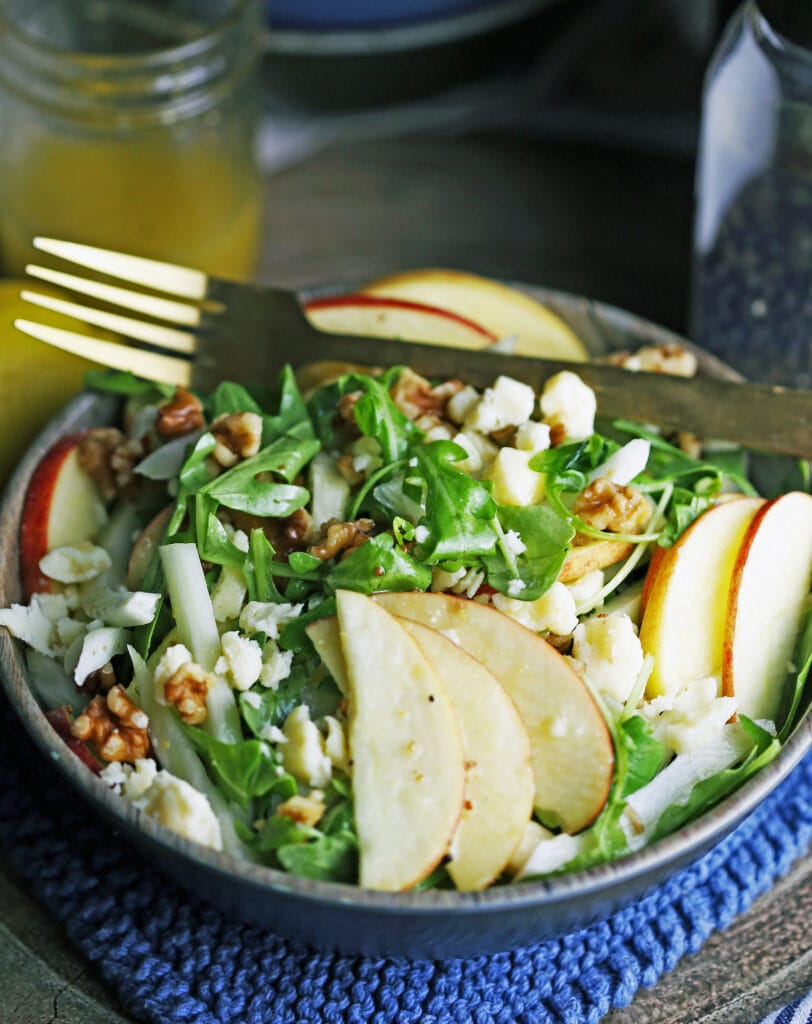 Apple fennel arugula salad in a brown bowl with a fork on top.