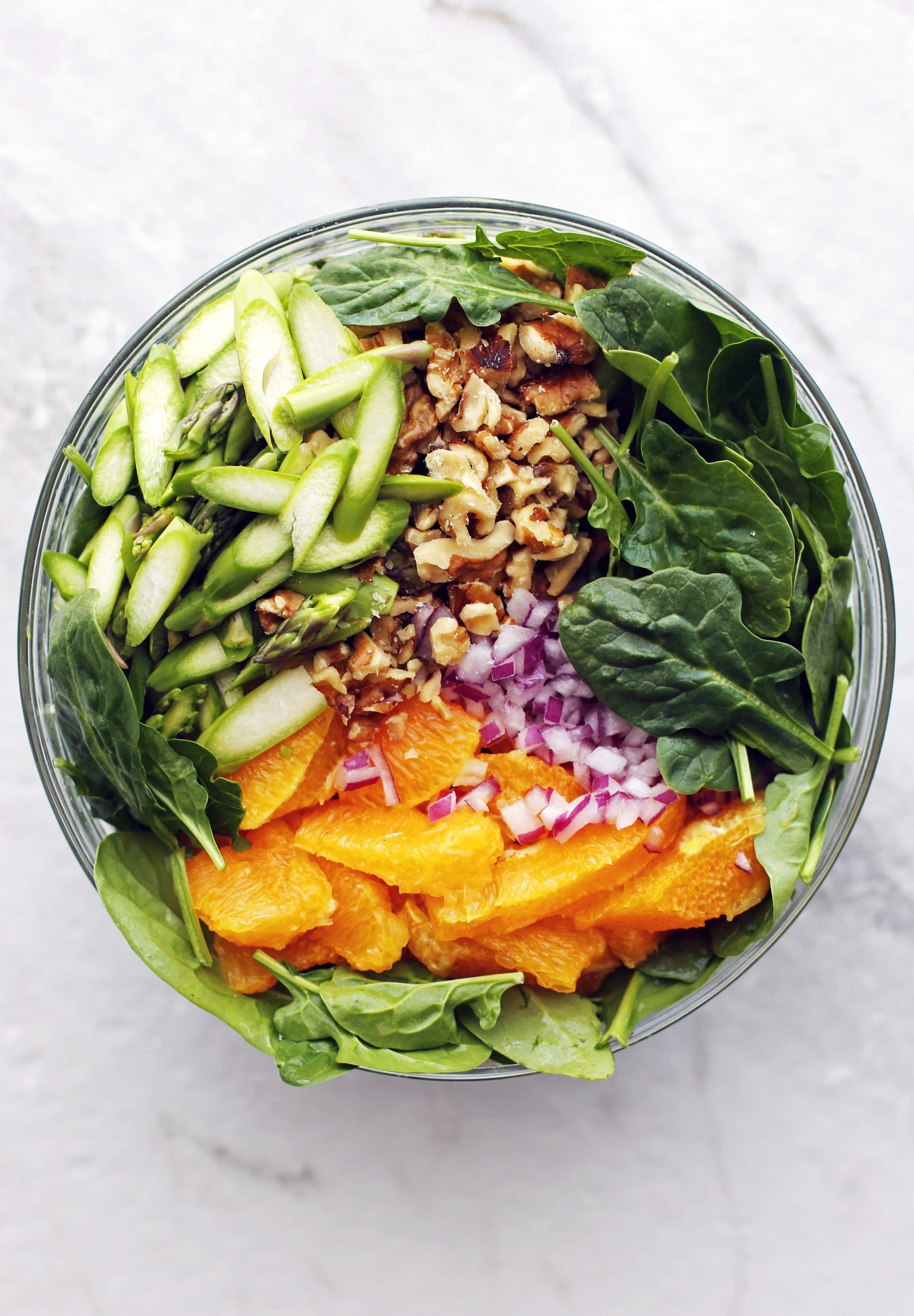 A glass bowl full of asparagus, spinach, orange, red onion, avocado, and walnuts.