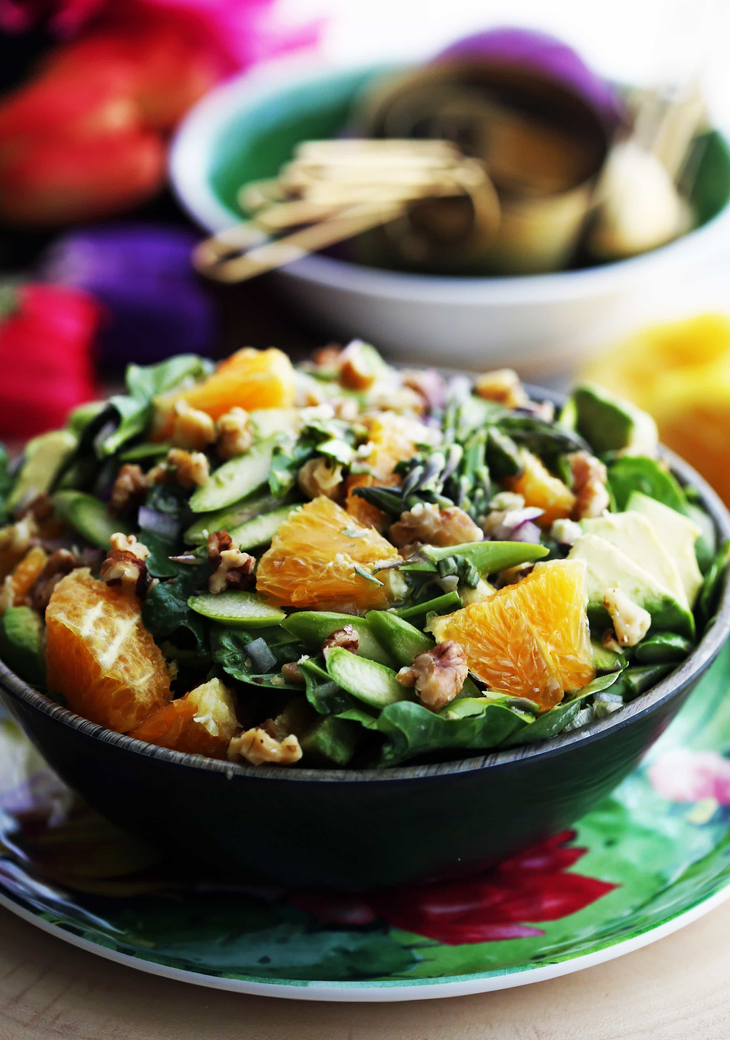 A closeup view of a bowl of Asparagus Orange Spinach Salad with Basil Lemon Vinaigrette