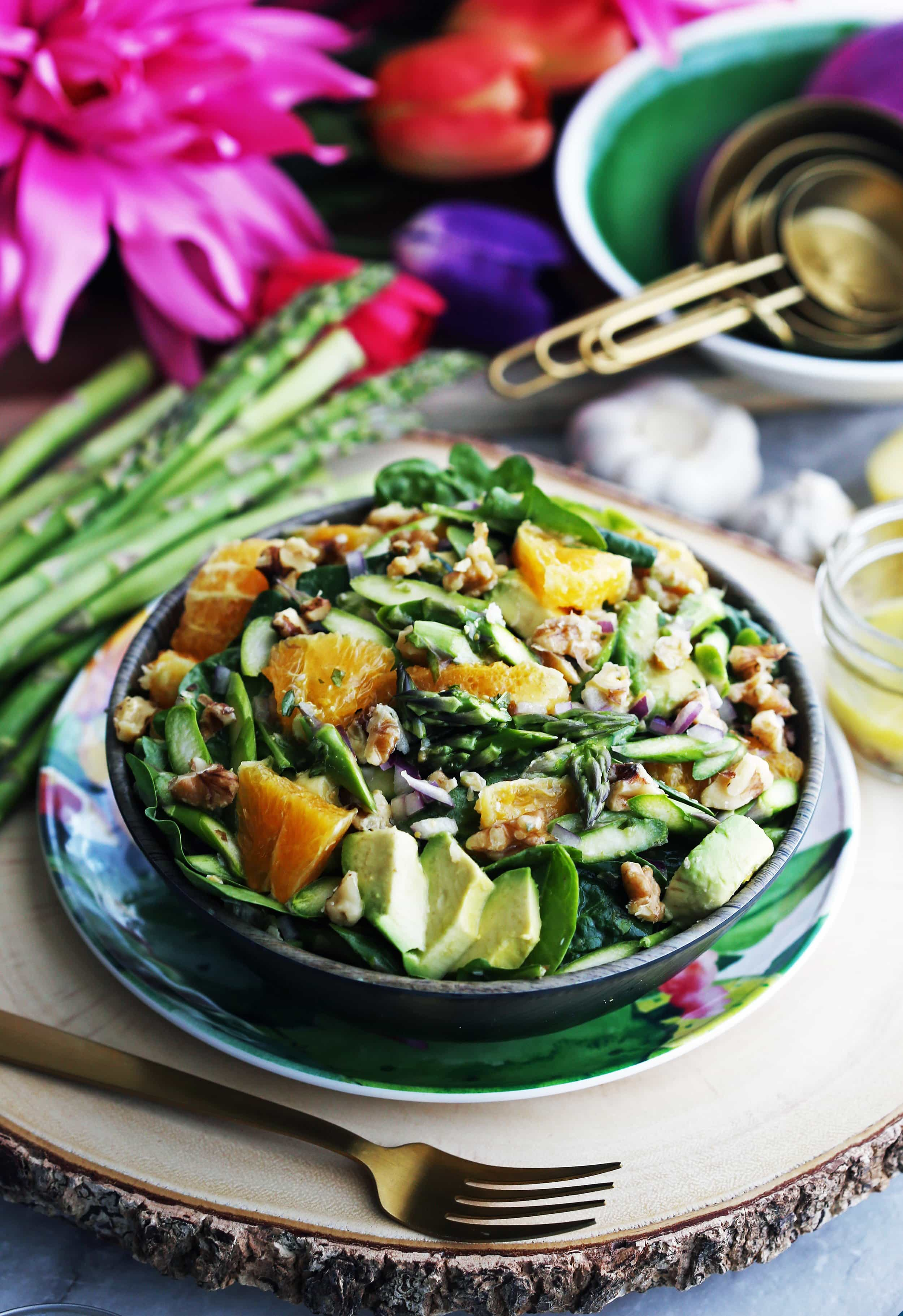 A wooden bowl full of Asparagus Orange Spinach Salad with Basil Lemon Vinaigrette along with a fork beside it.