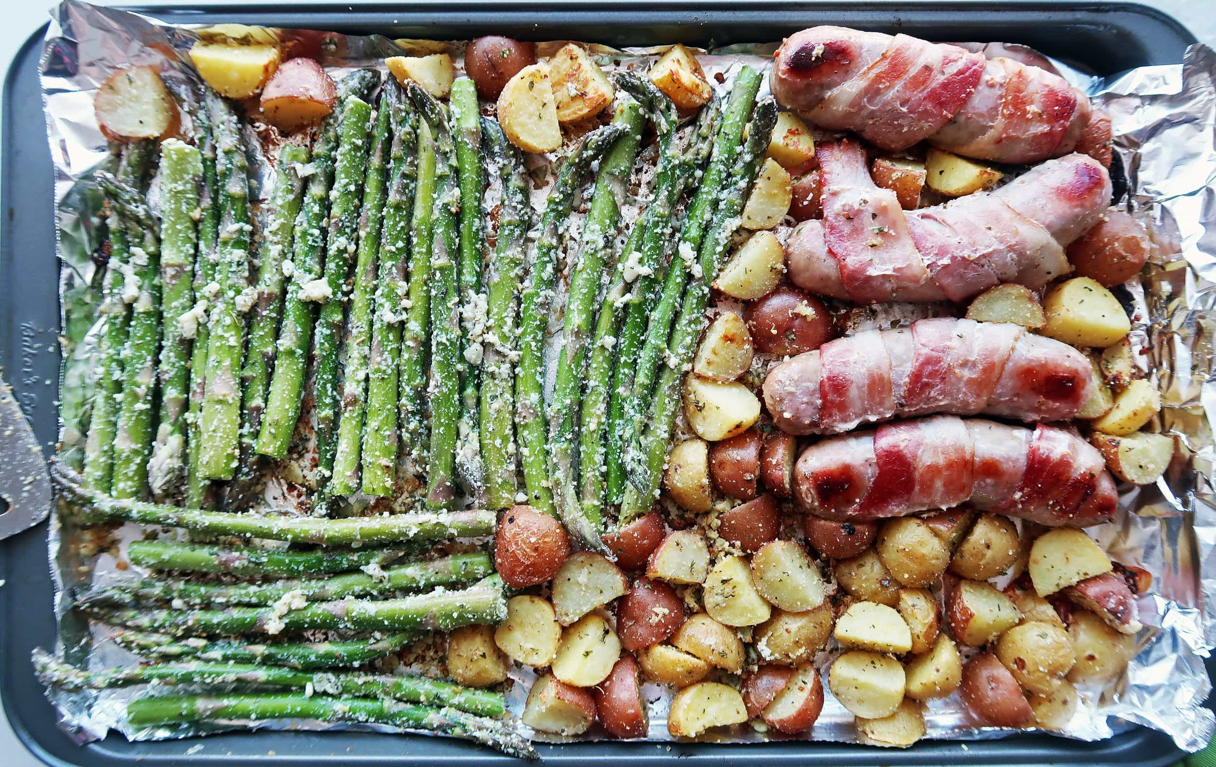 Bacon-wrapped sausages and vegetables on a baking sheet.