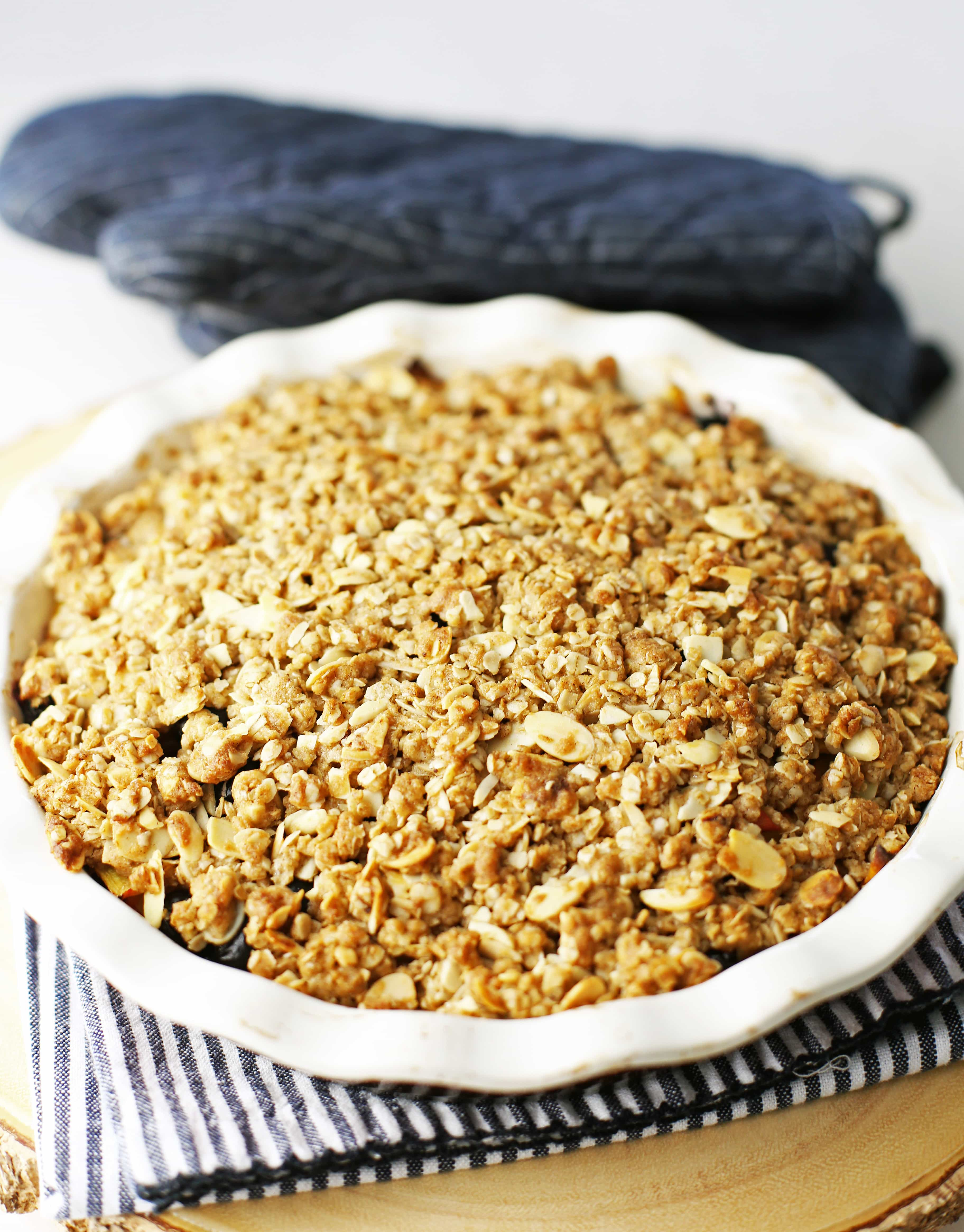 Baked blueberry peach crisp with almond oat topping in a pie dish on top of a white and blue towel.