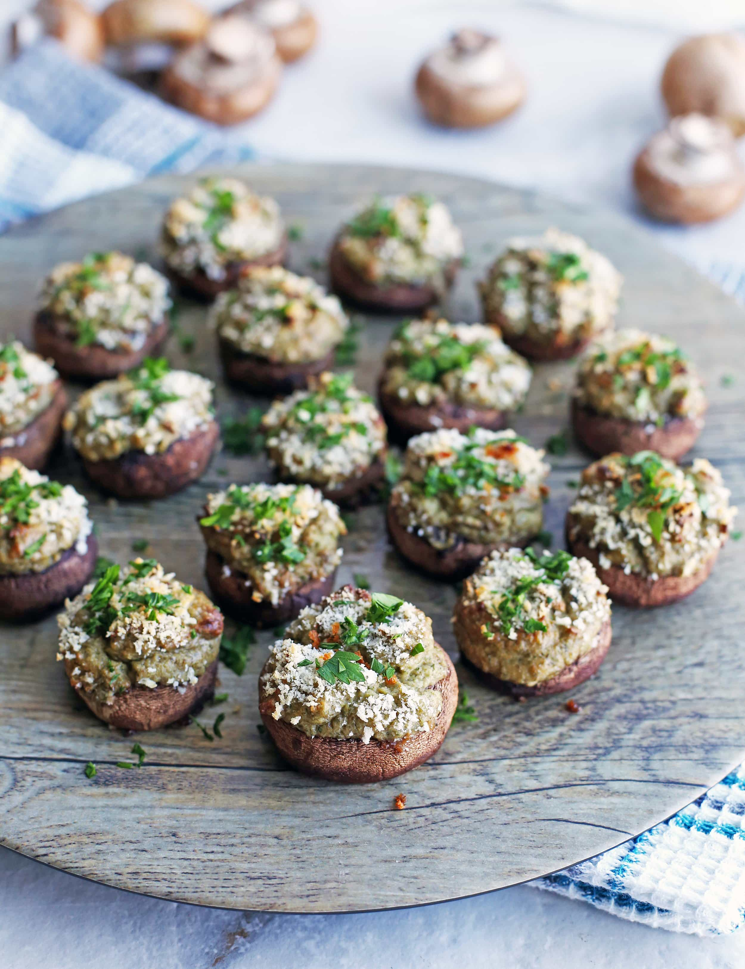 Over a dozen Baked Cheese Stuffed Mushrooms topped with breadcrumbs and chopped parsley on a round platter.