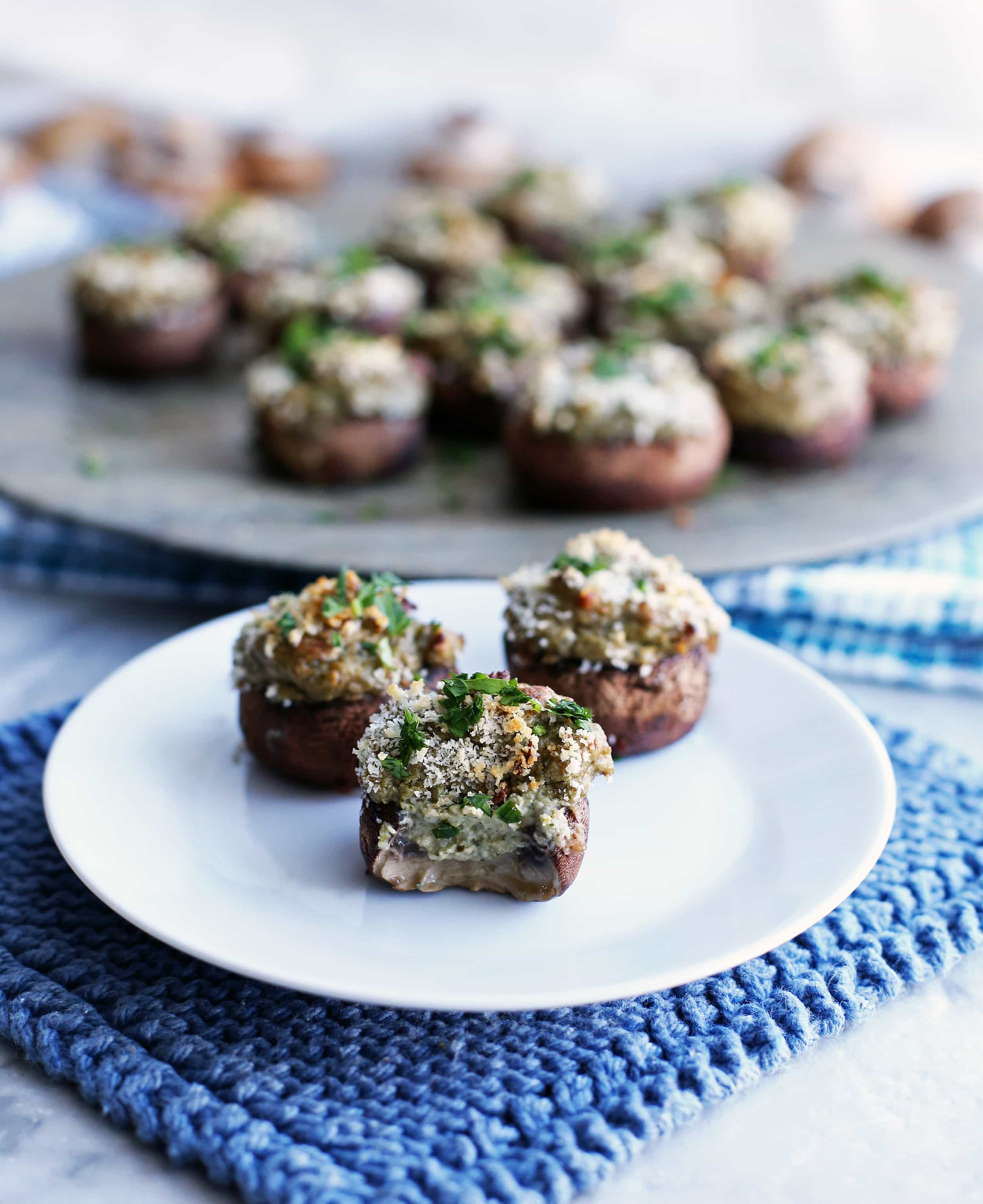 Three baked cheese stuffed mushrooms on a white plate with a bite taken out of one.