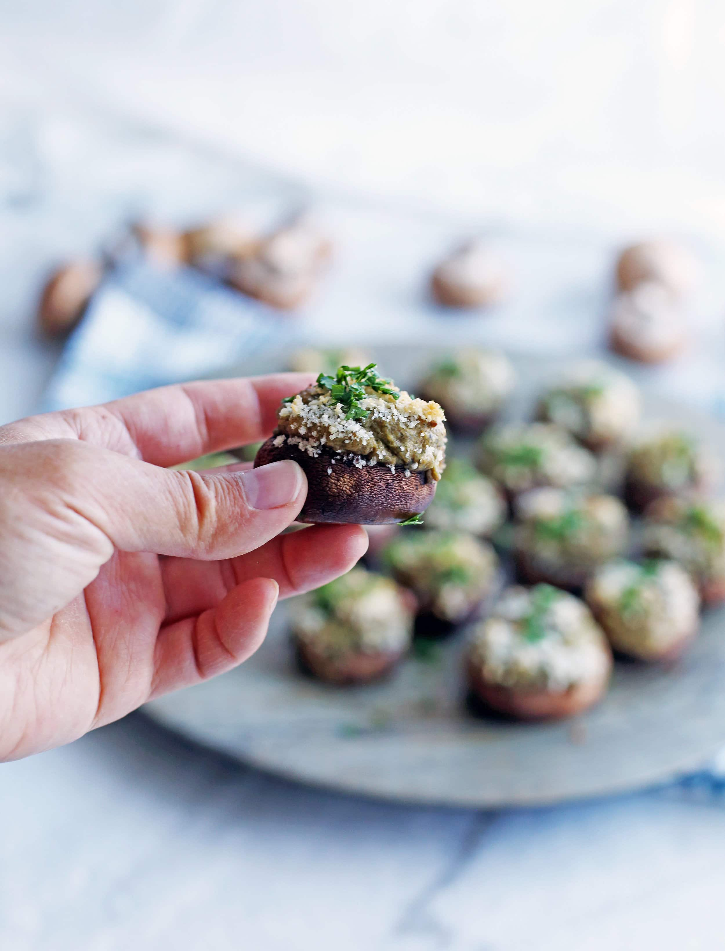 A hand holding a single baked stuffed mushroom on top of a platter containing more stuffed mushrooms.