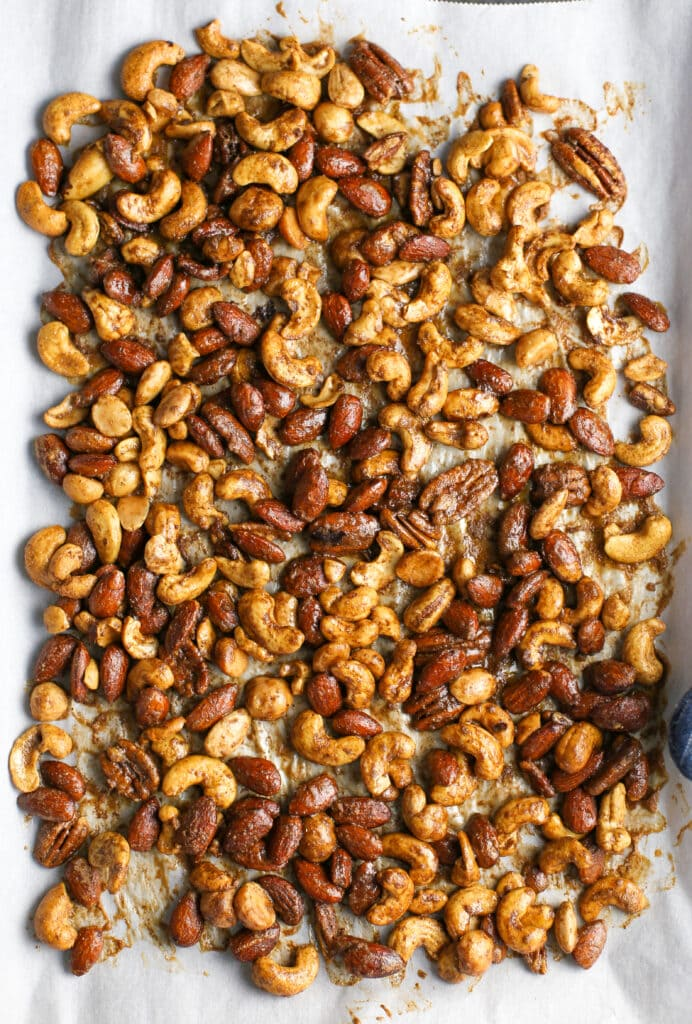 Baked cinnamon sugar mixed nuts spread in a single layer in a large baking sheet.