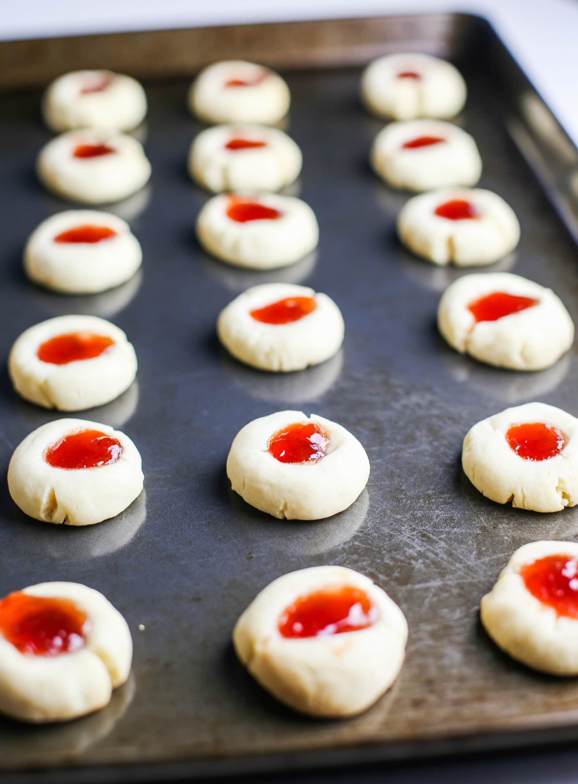 Baked condensed milk thumbprint cookies filled with strawberry jam on a baking sheet.