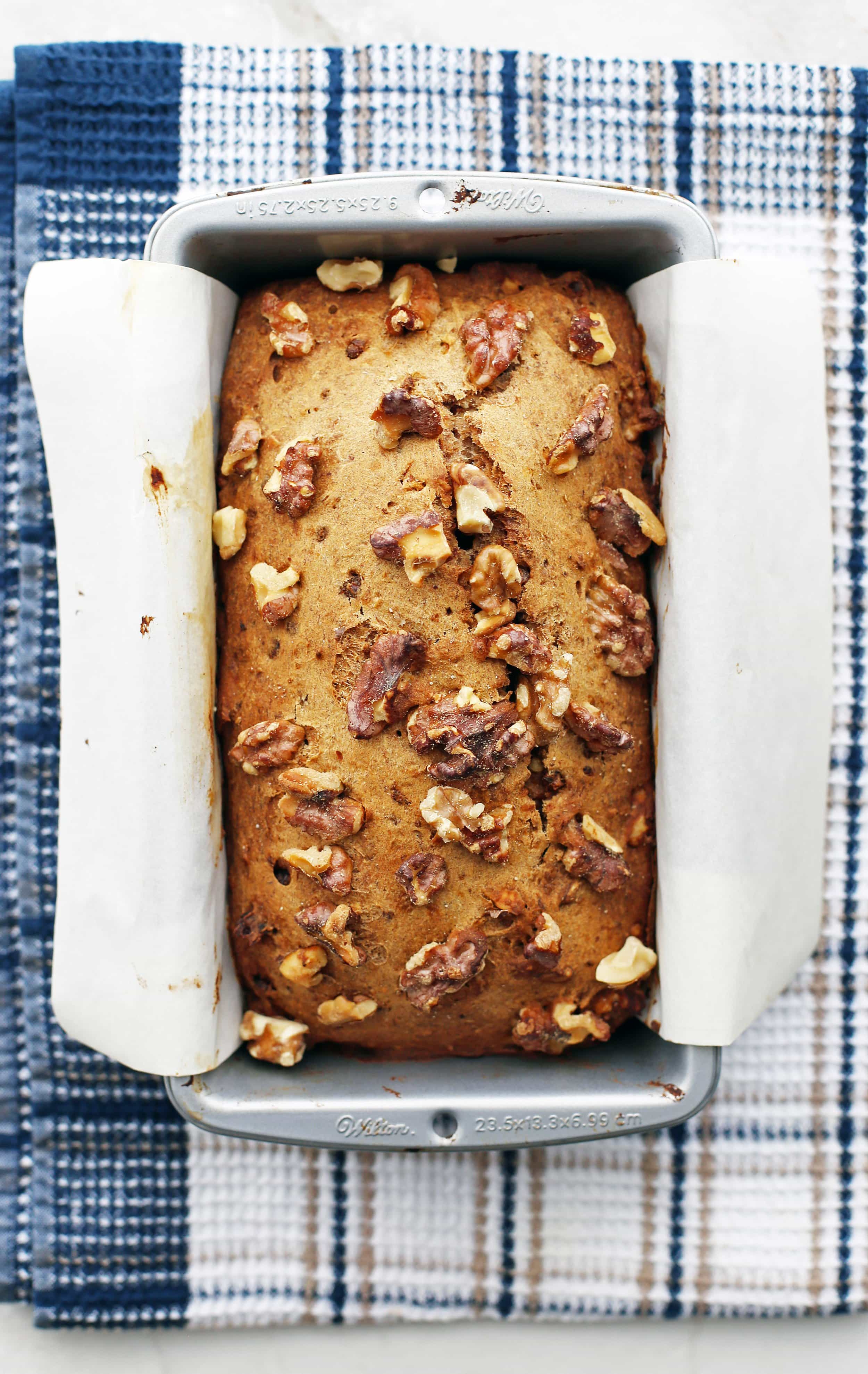 Freshly baked Date Banana Nut Bread in a parchment paper-lined loaf pan.