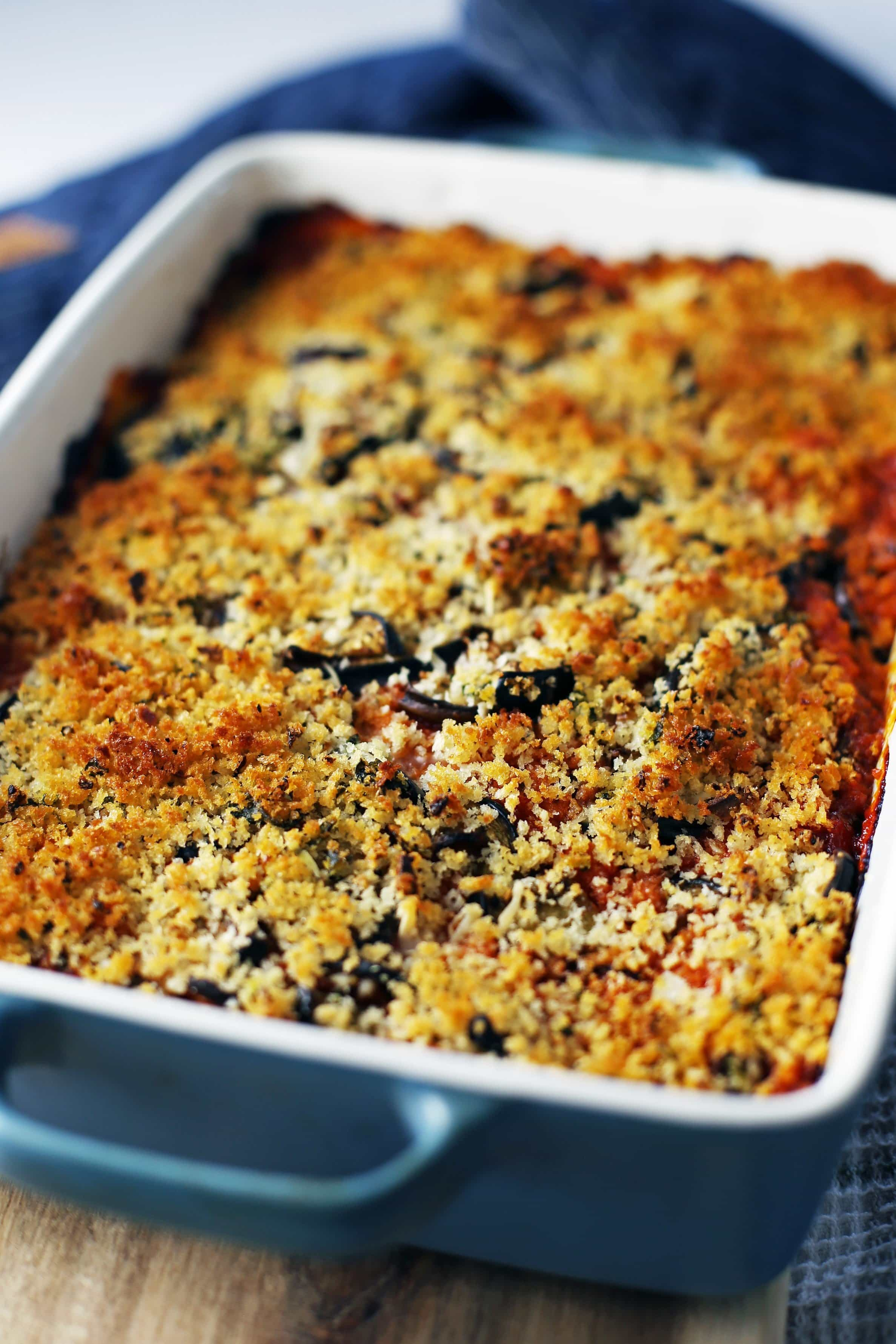 Baked Eggplant Parmesan Casserole with a golden-brown Panko breadcrumb topping in a large blue rectangular dish.