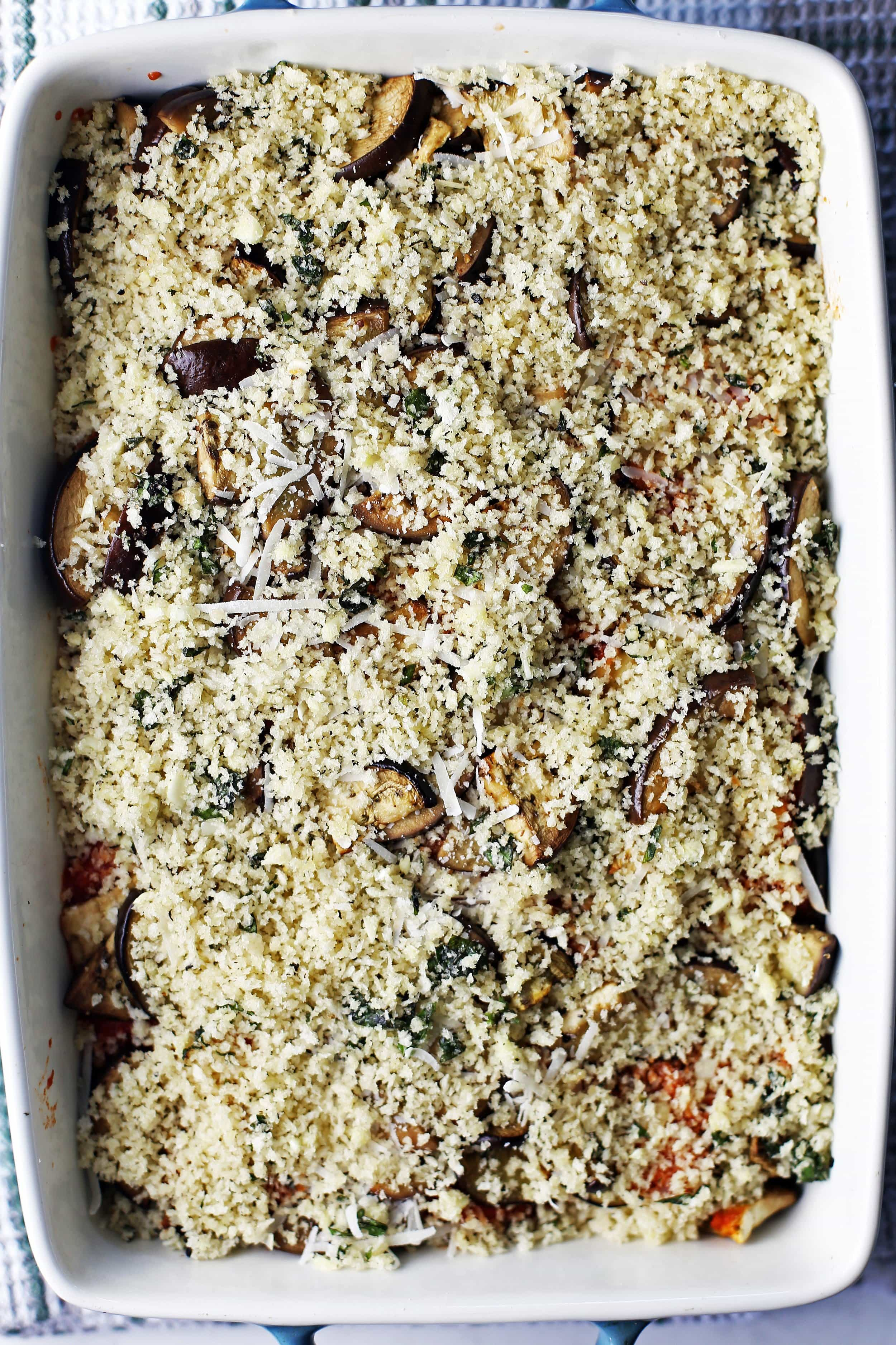 A large casserole dish containing three layers of marinara sauce, sliced eggplant, herbs, and cheeses with a breadcrumb topping.