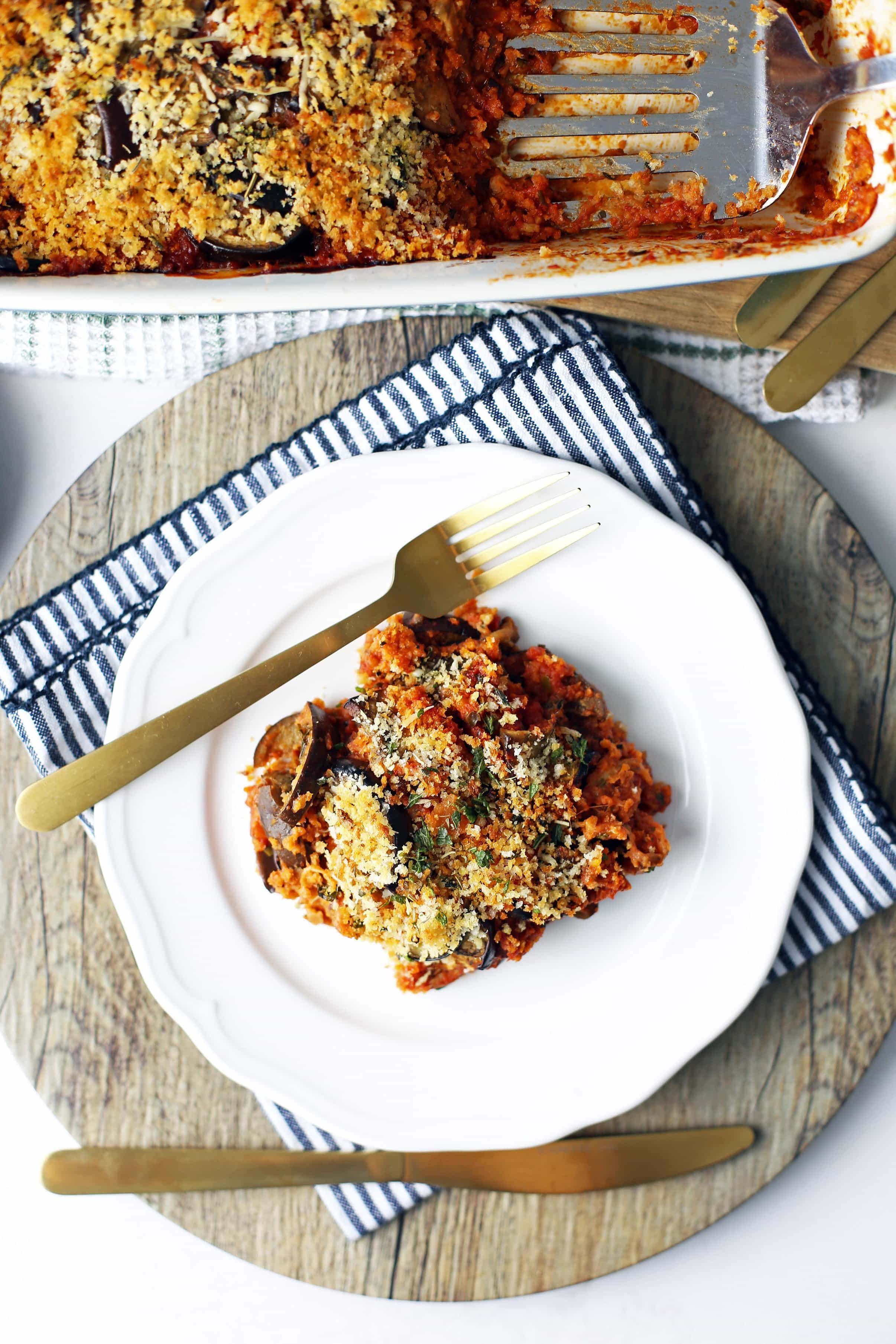 Overhead view of Baked Eggplant Parmesan on a white plate and large rectangular dish.