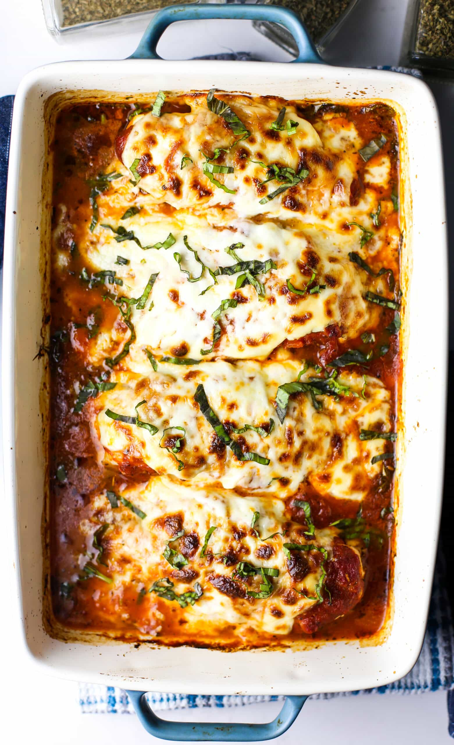 Baked mozzarella chicken with marinara sauce in a casserole dish.