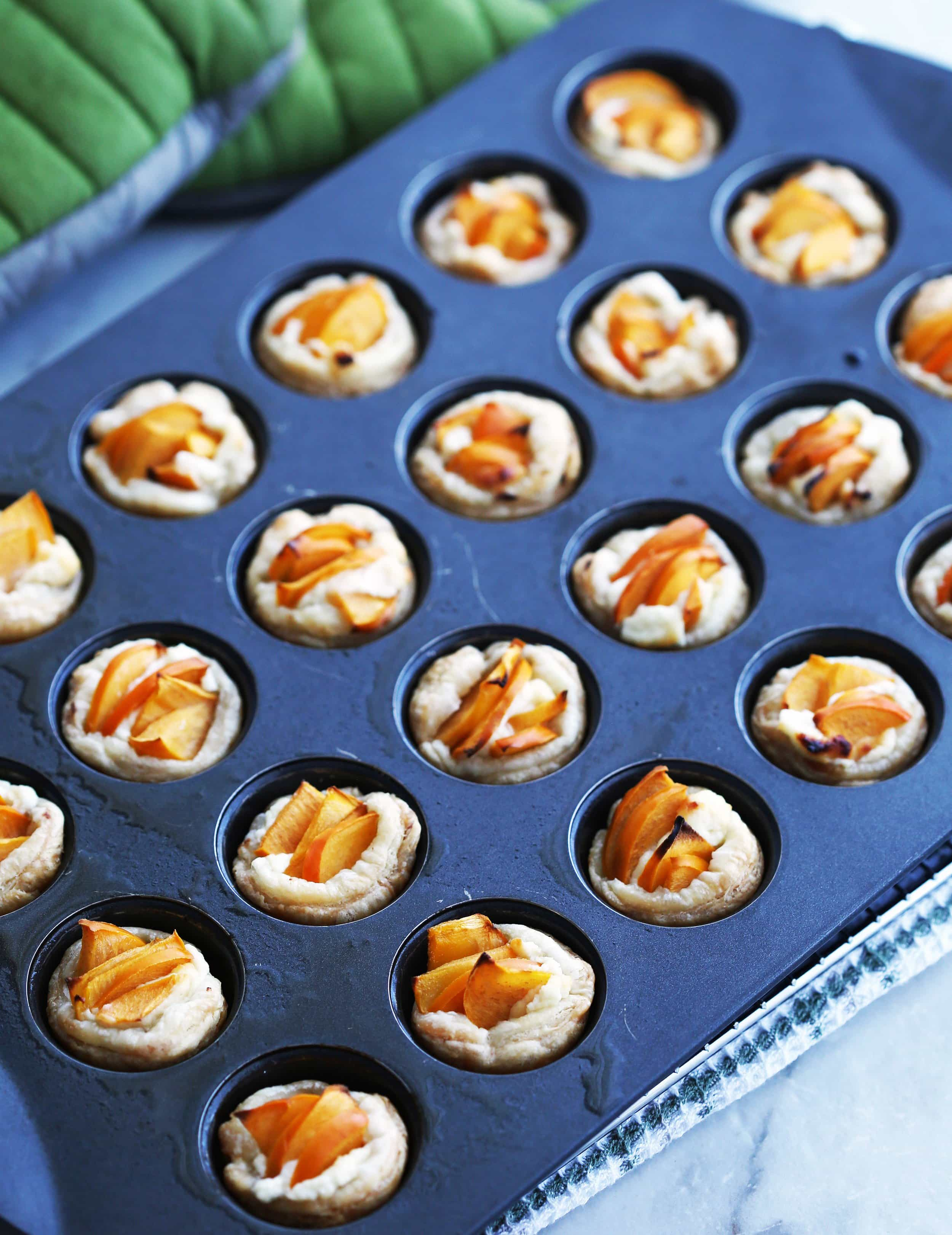 Baked Persimmon Goat Cheese Tartlets in a mini muffin pan.