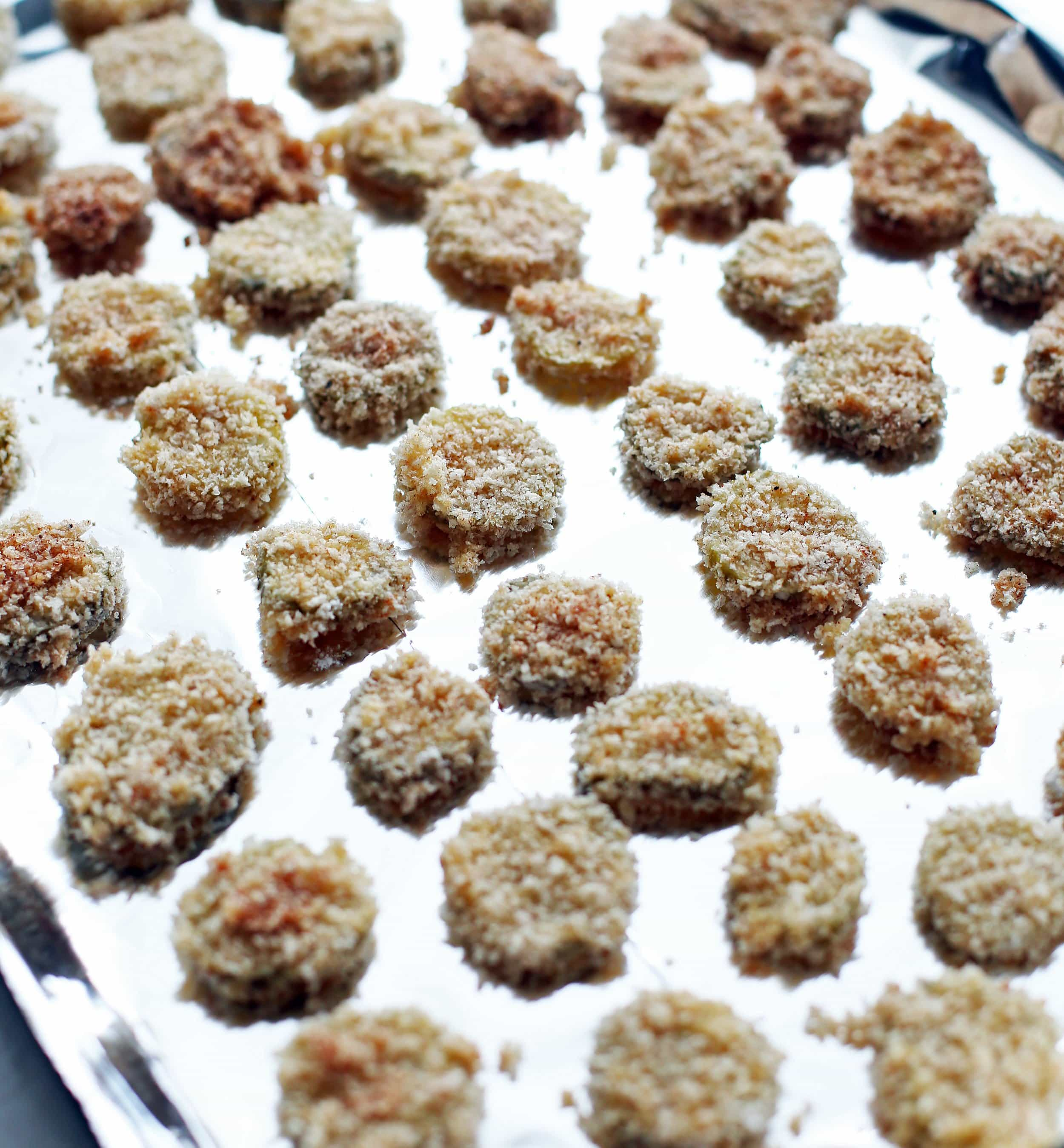 Dredged panko breadcrumb covered pickle slices placed on an aluminum foil lined baking sheet.