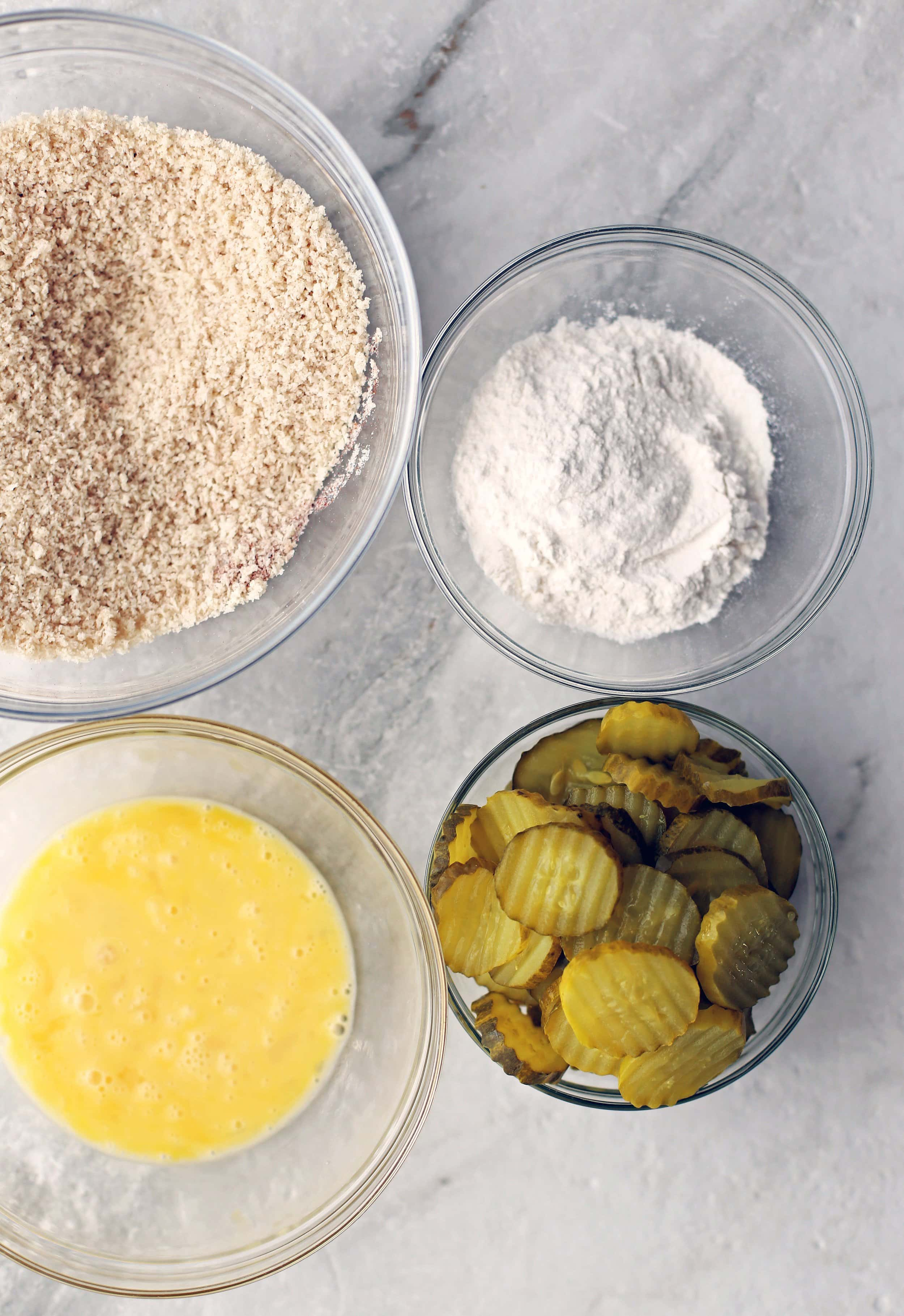 An overhead view of four glass bowls filled with pickle slices, beaten eggs, flour, and panko breadcrumbs.