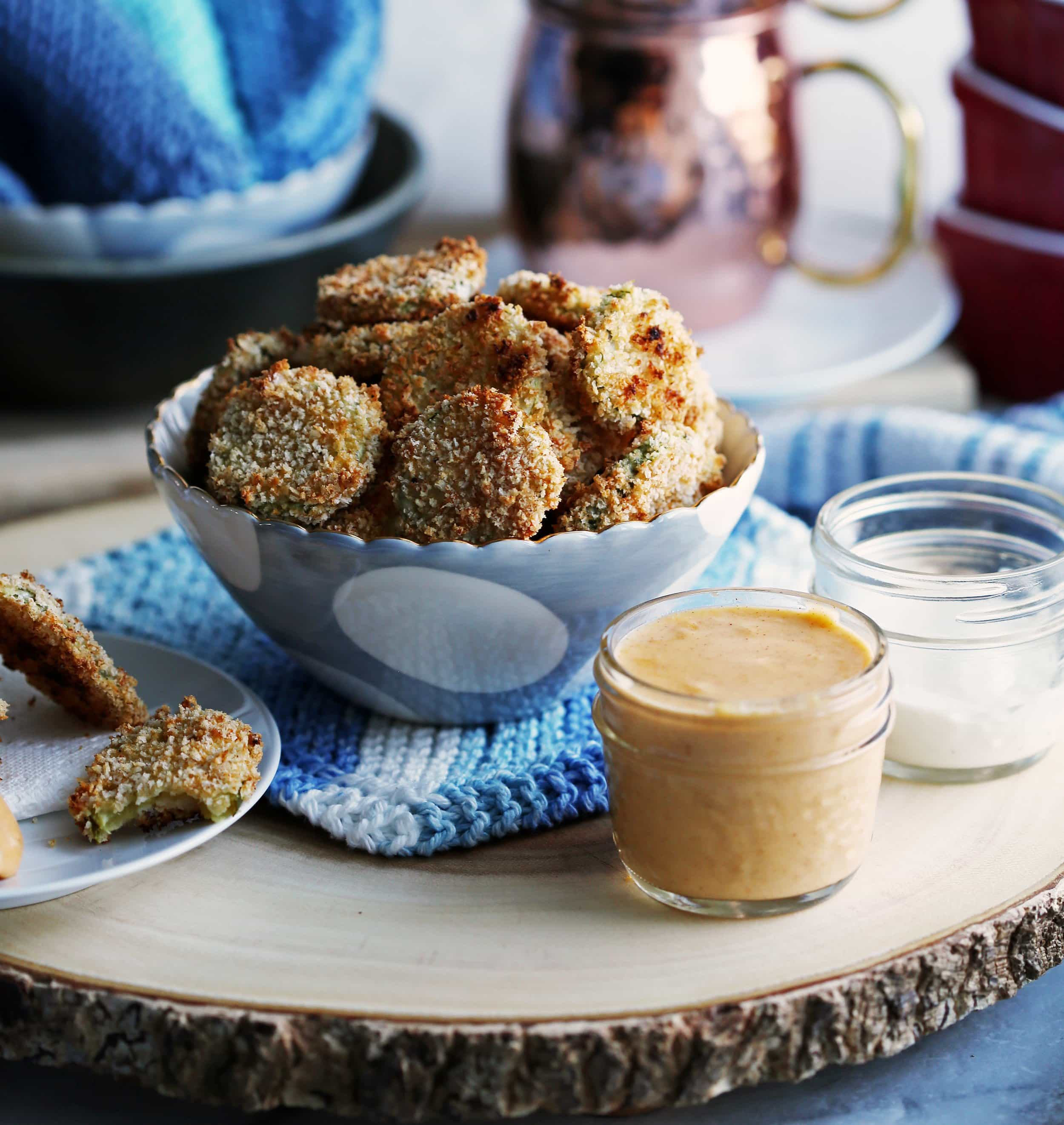 A blue bowl of crispy oven-fried pickles slices with a jar of creamy cheddar dip on the side.