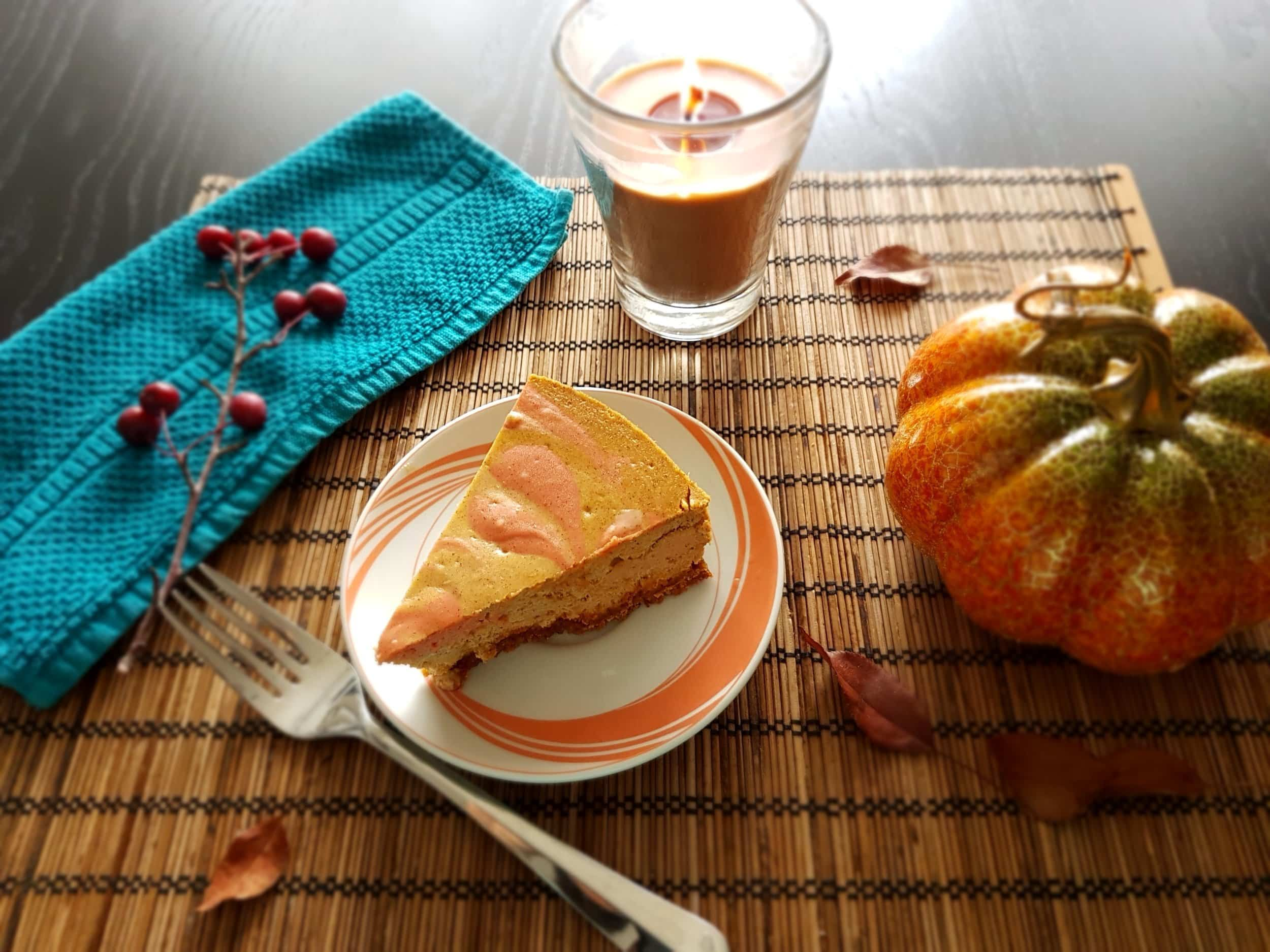 A slice of Baked Pumpkin Cheesecake surrounded by autumn decor.