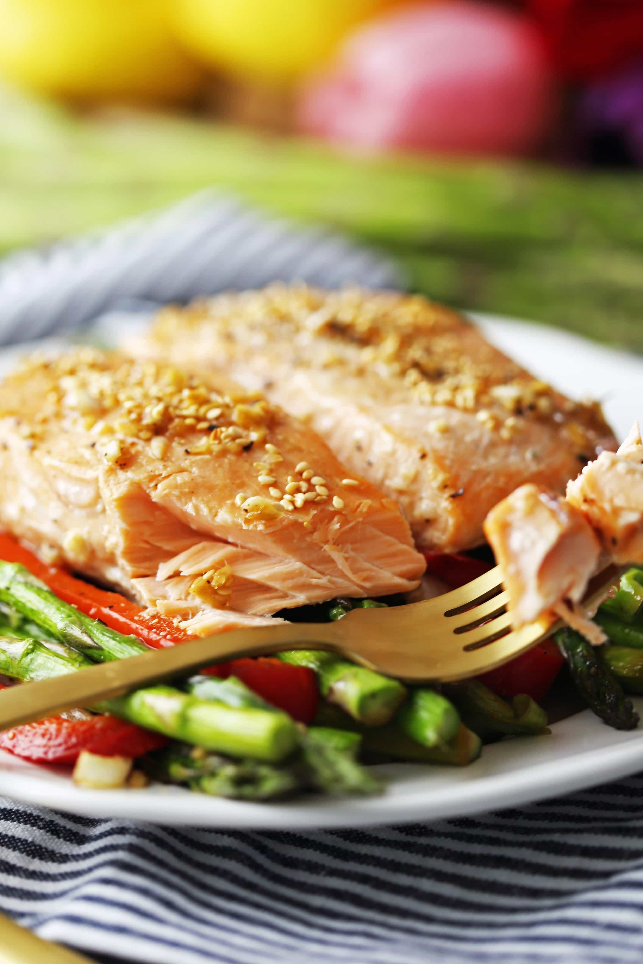 A flaky piece of baked salmon on the tines of a gold fork that's placed on a white plate with two salmon fillets, asparagus, and bell peppers.