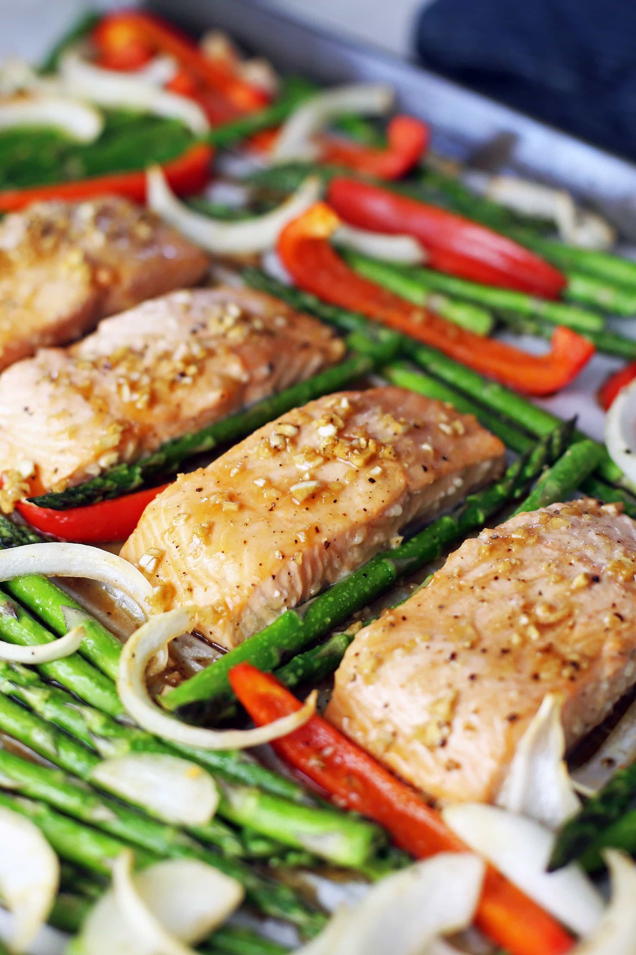 Four baked marinated salmon fillets in a row with roasted asparagus, bell pepper, and onions surrounding them on a large baking sheet.