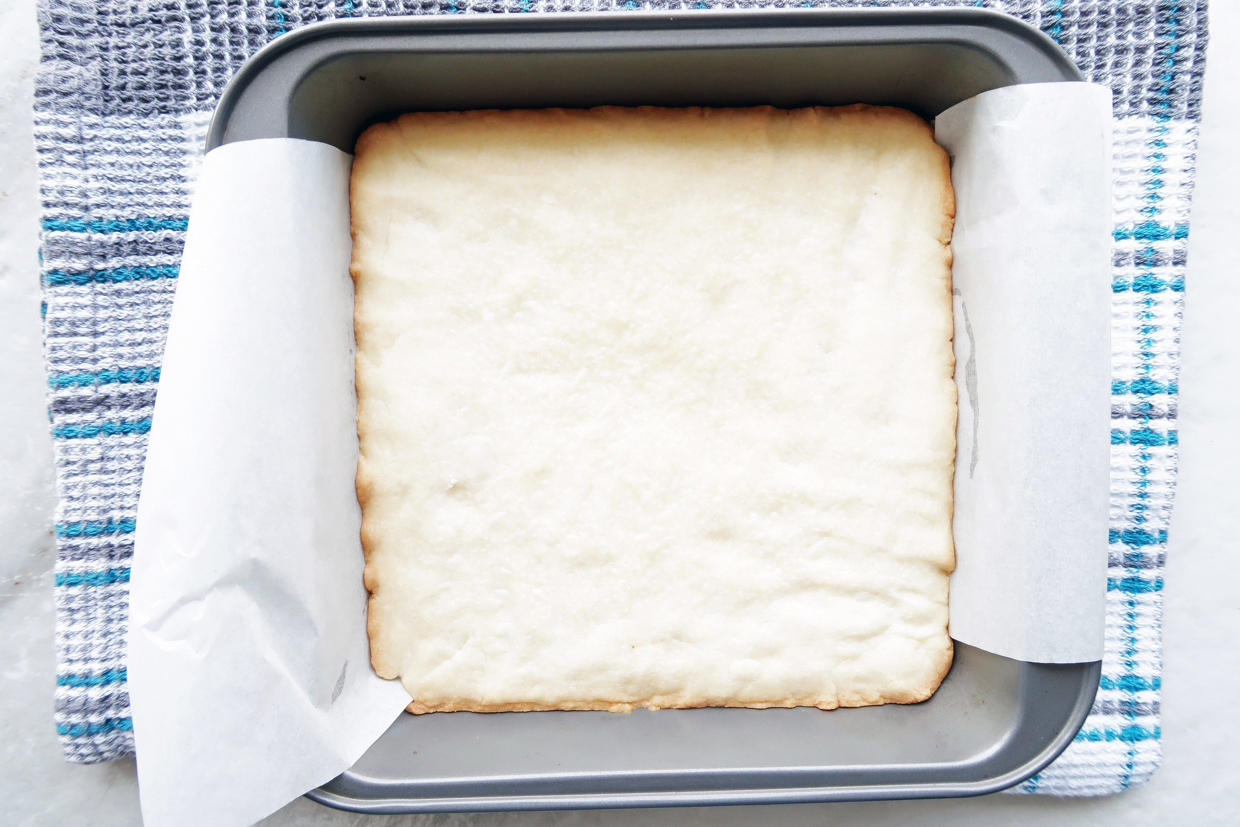 Baked shortbread in a parchment paper-lined square baking pan.