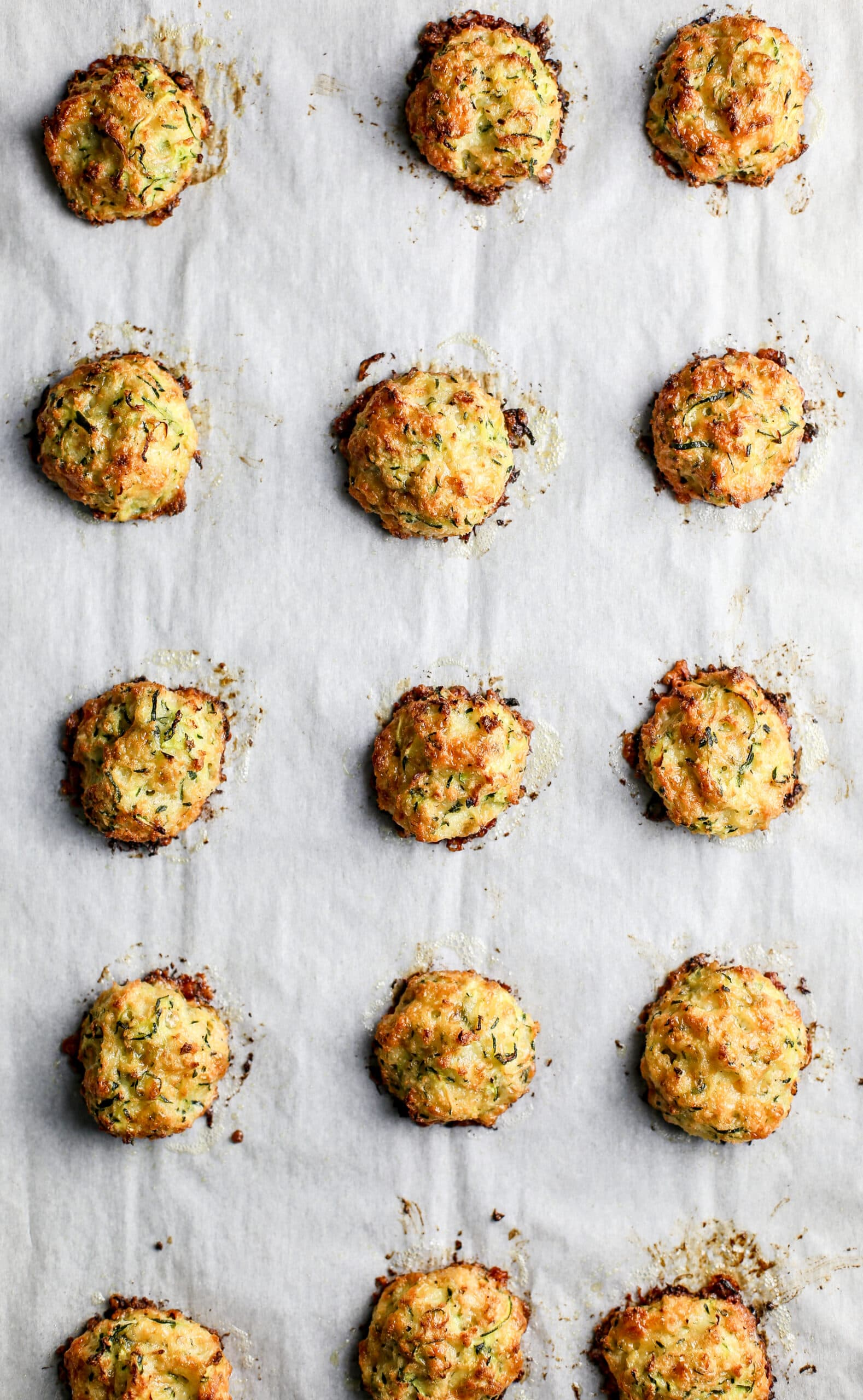 Baked zucchini bites on top of a parchment paper lined baking sheet.