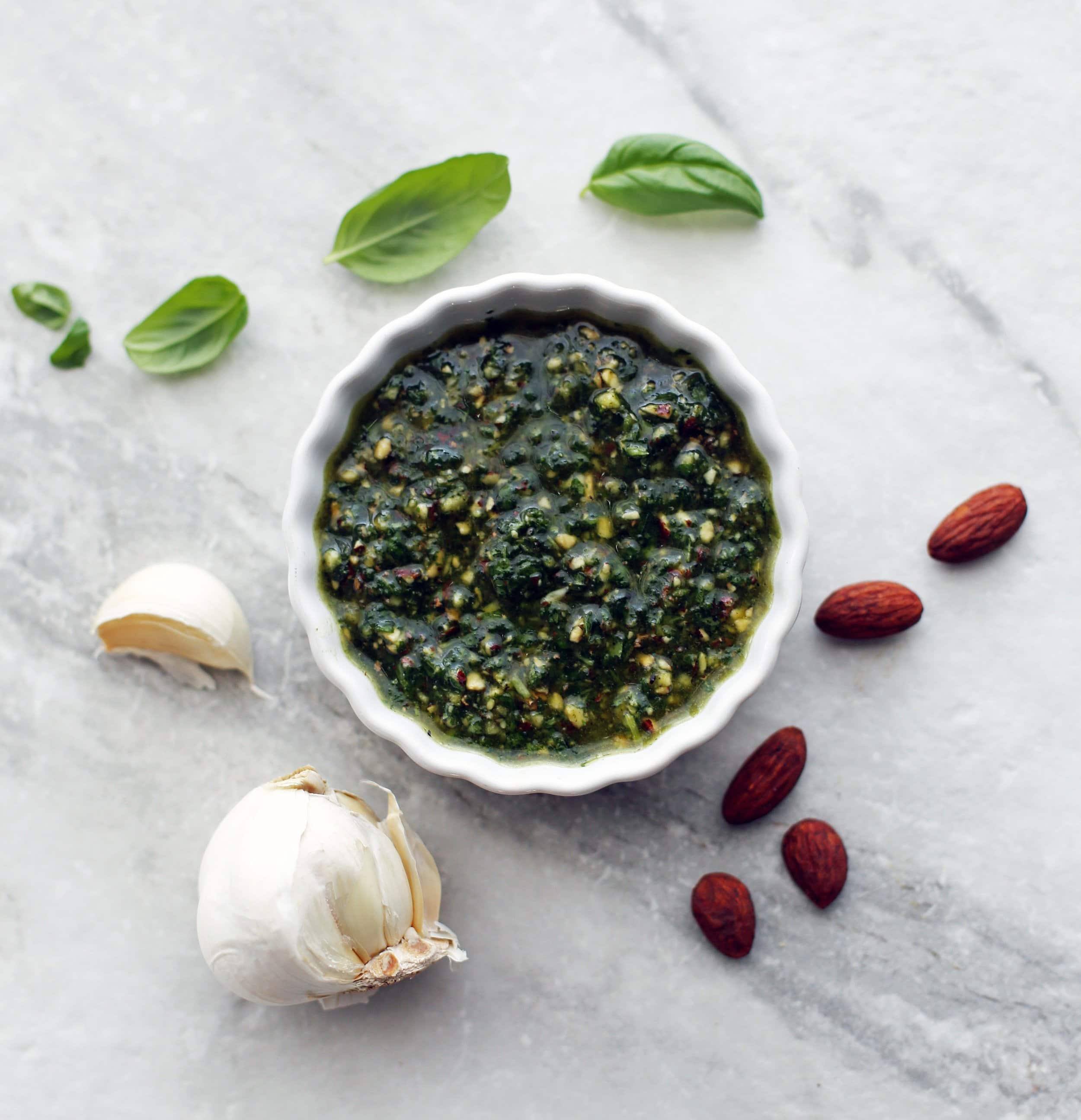 Dark green basil almond pesto in a small white bowl with basil leaves, almonds, and garlic around it.
