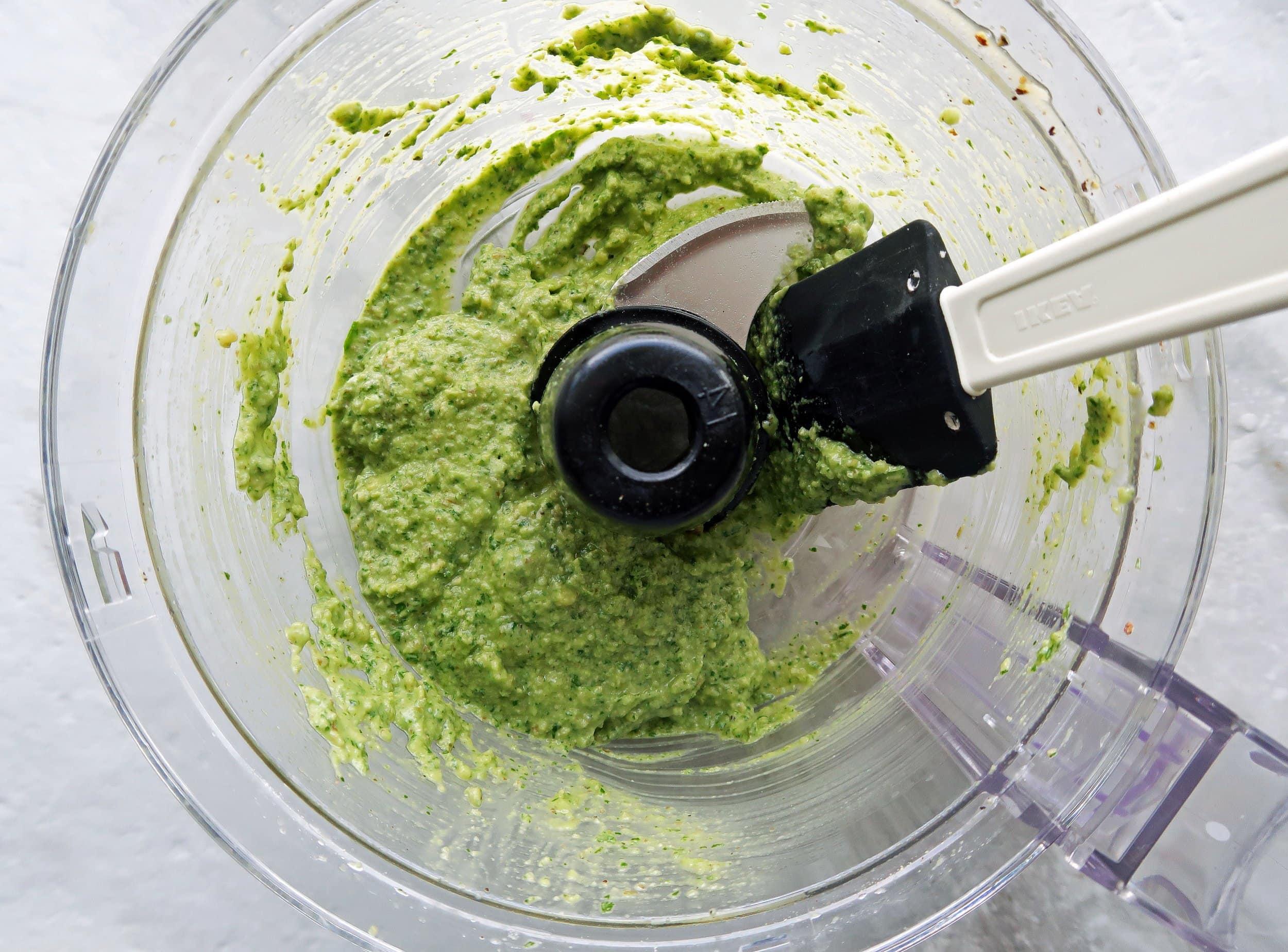 Creamy fresh basil avocado pesto in a food processor.
