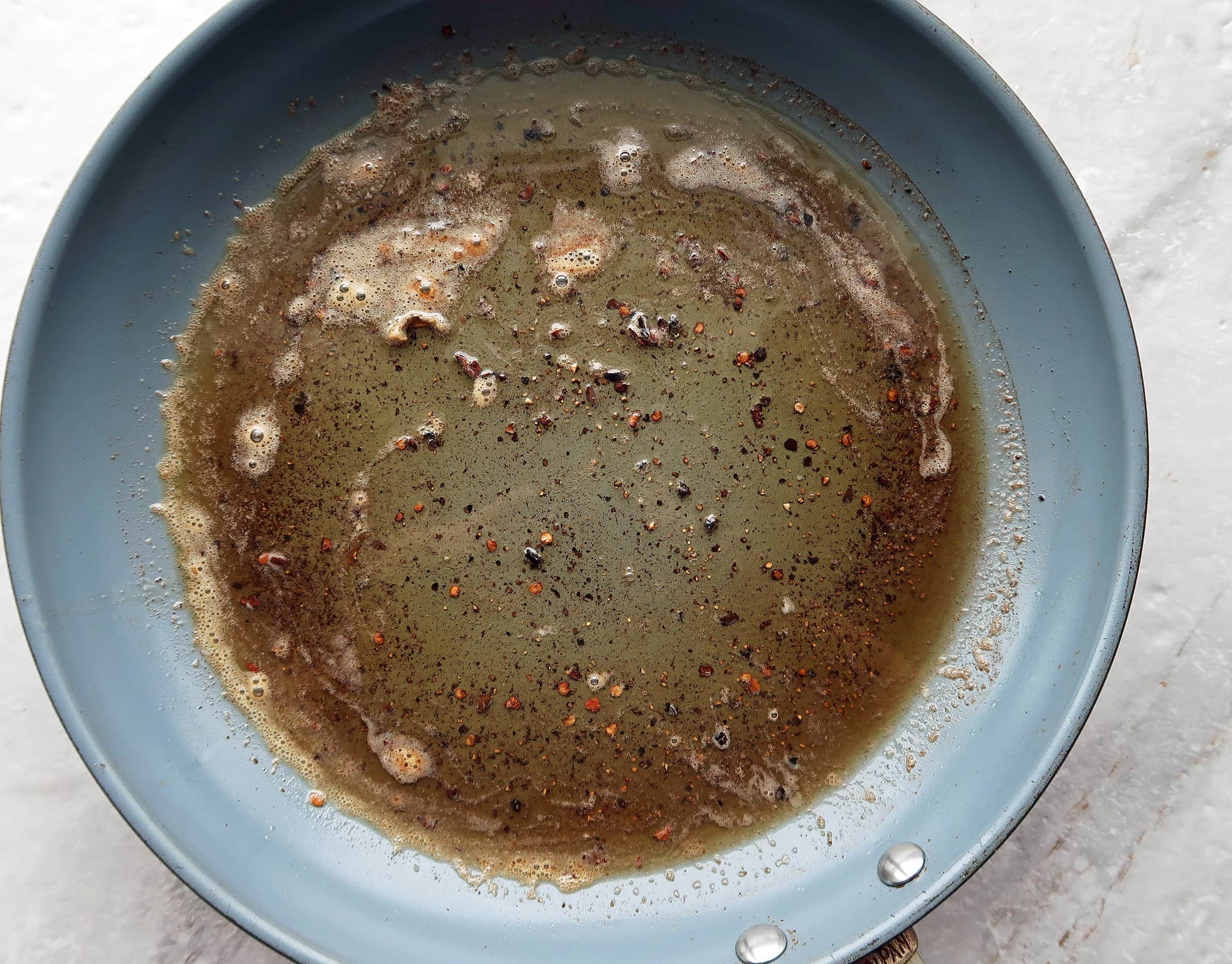 A skillet with melted butter, olive oil, black pepper, and red pepper flakes.