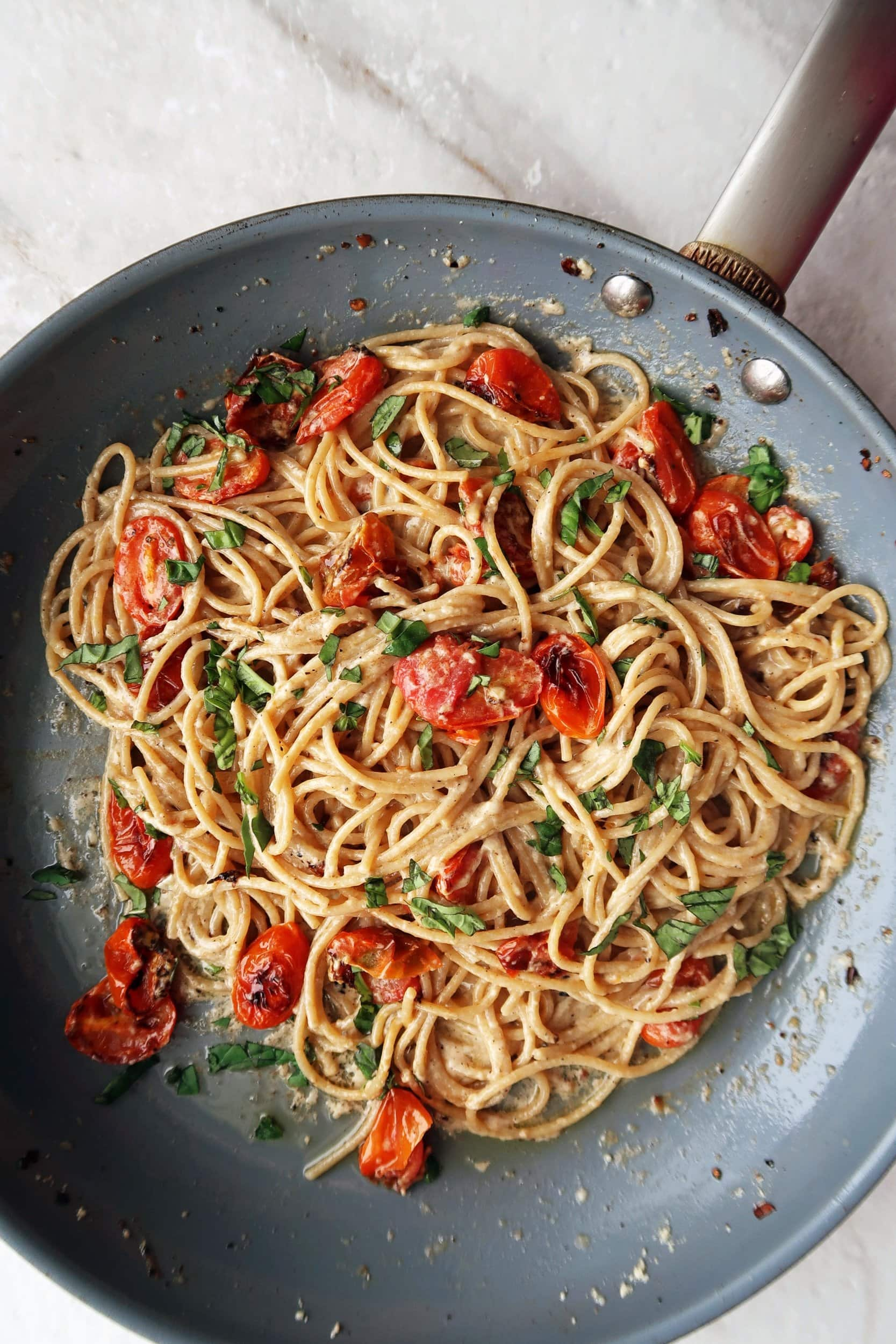 Black pepper and parmesan spaghetti (cheese and pepper pasta) with garlic roasted tomatoes tossed in a skillet.