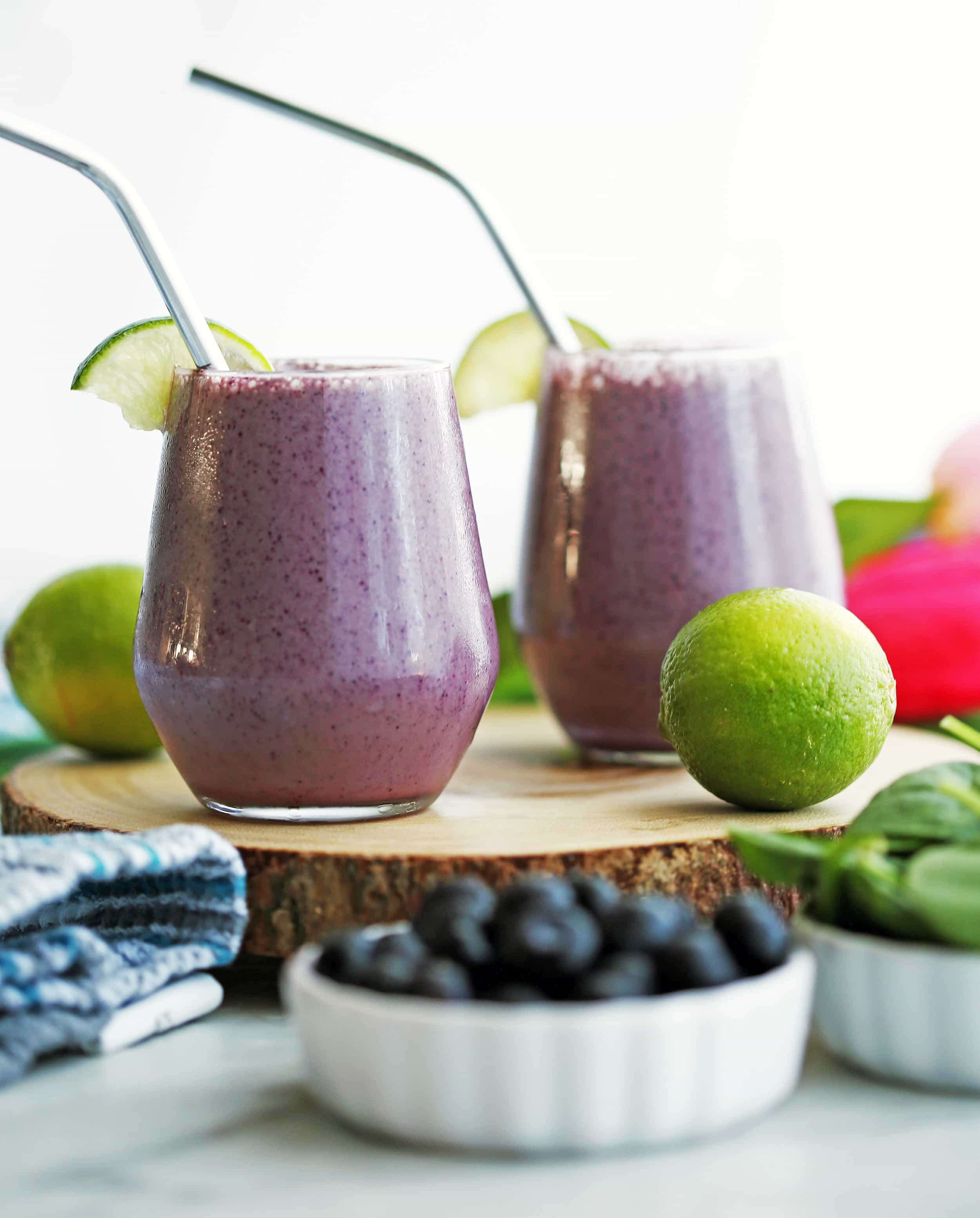 Two Blueberry Lime Yogurt Smoothies with lime wedges and straws on a wooden board.