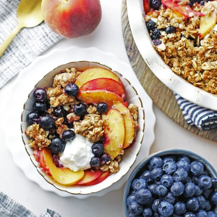 Overhead view of a bowl of blueberry peach crisp with more on the side.