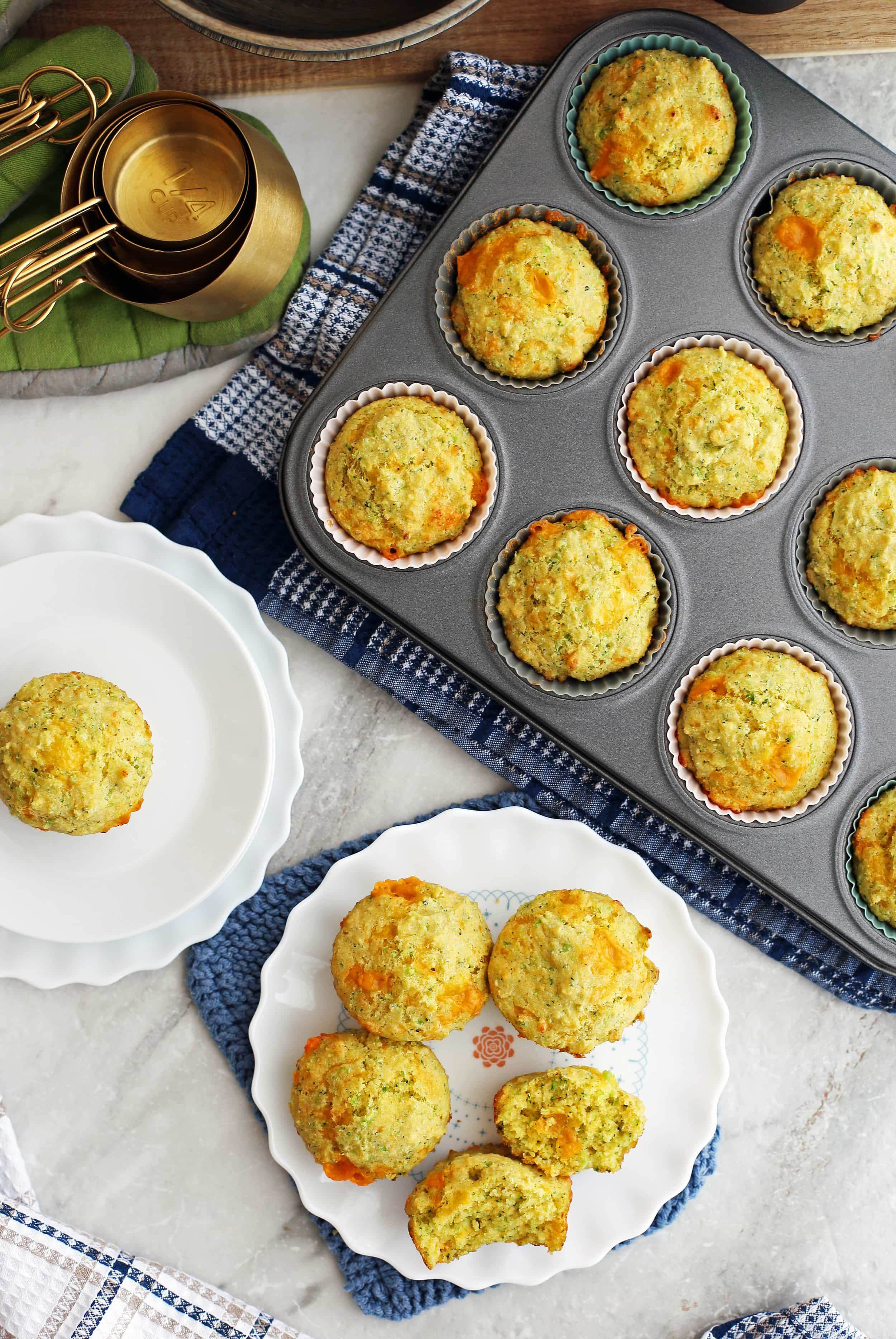 Overhead view of Broccoli Cheddar Cornbread Muffins on two white plates and a muffin pan.