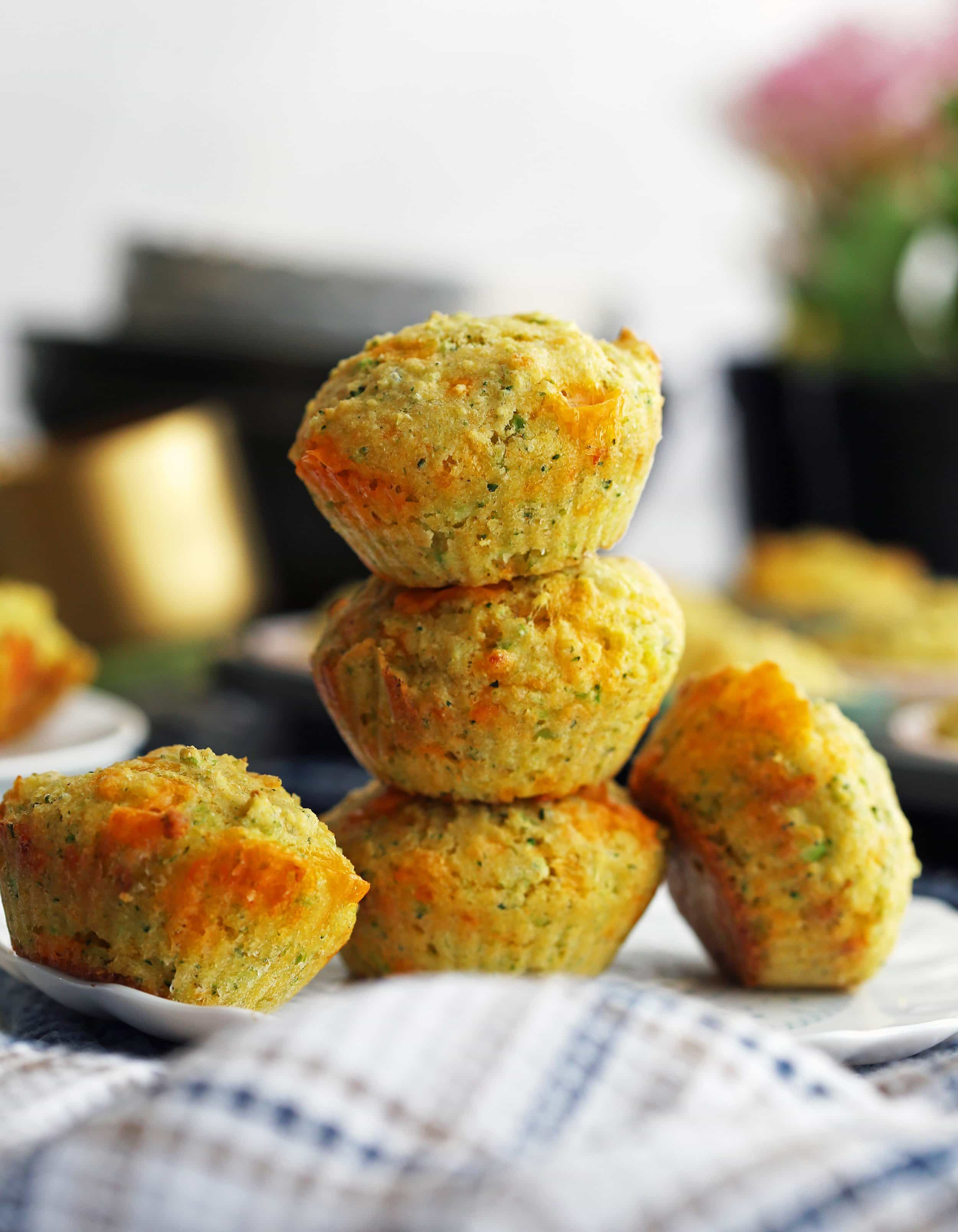 A side view of three Broccoli Cheddar Cornbread Muffins stacked on top one another with two more muffins on the side.