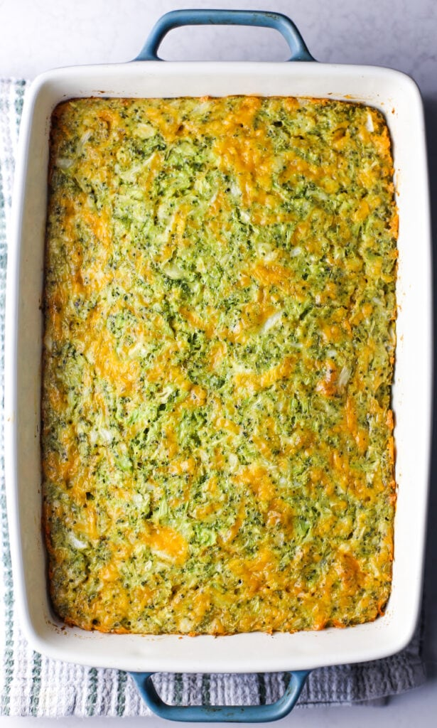 Freshly baked broccoli cheddar squares (pre-sliced) in a rectangular baking dish.