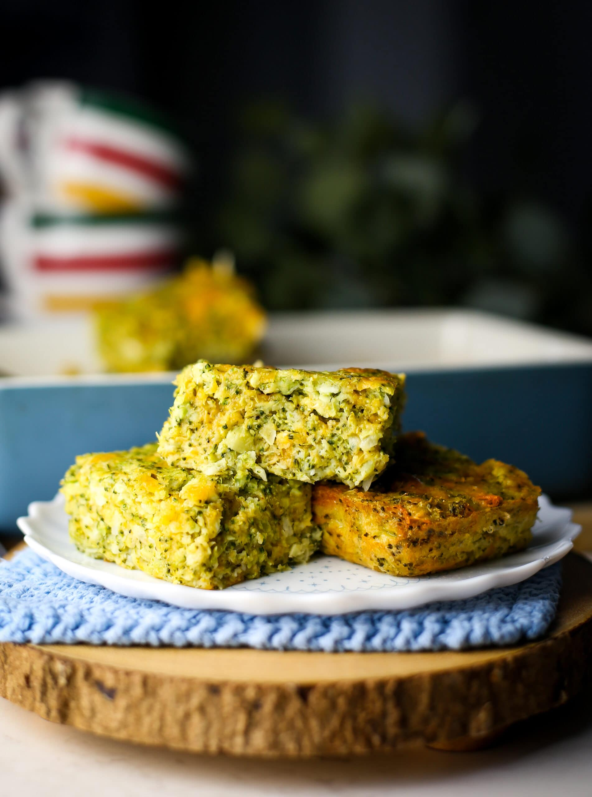 Three broccoli cheddar squares piled on a white plate.